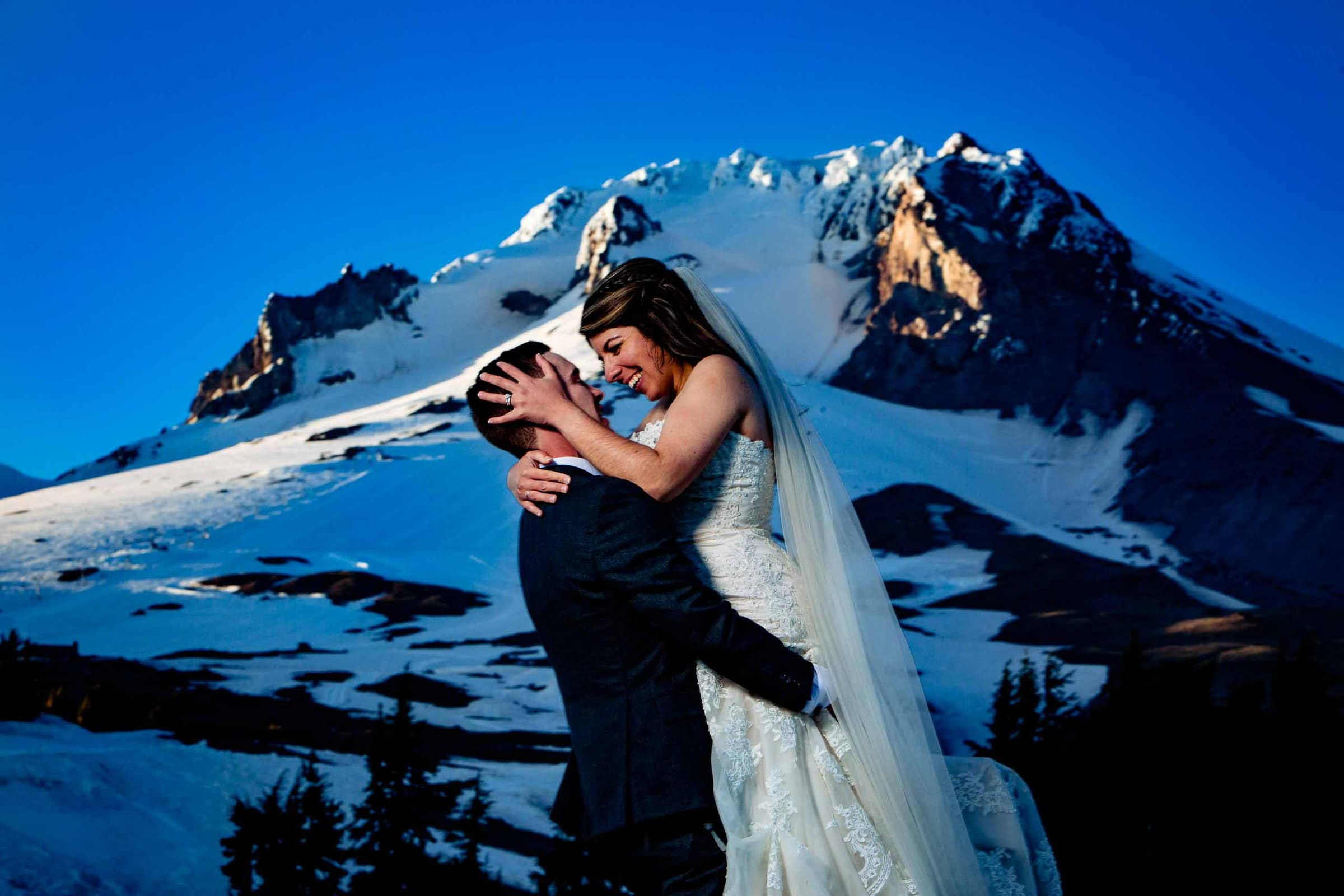 Bride and groom hugging and holding each other in the sun with Mt Hood in the background moments after their Timberline Lodge Wedding ceremony