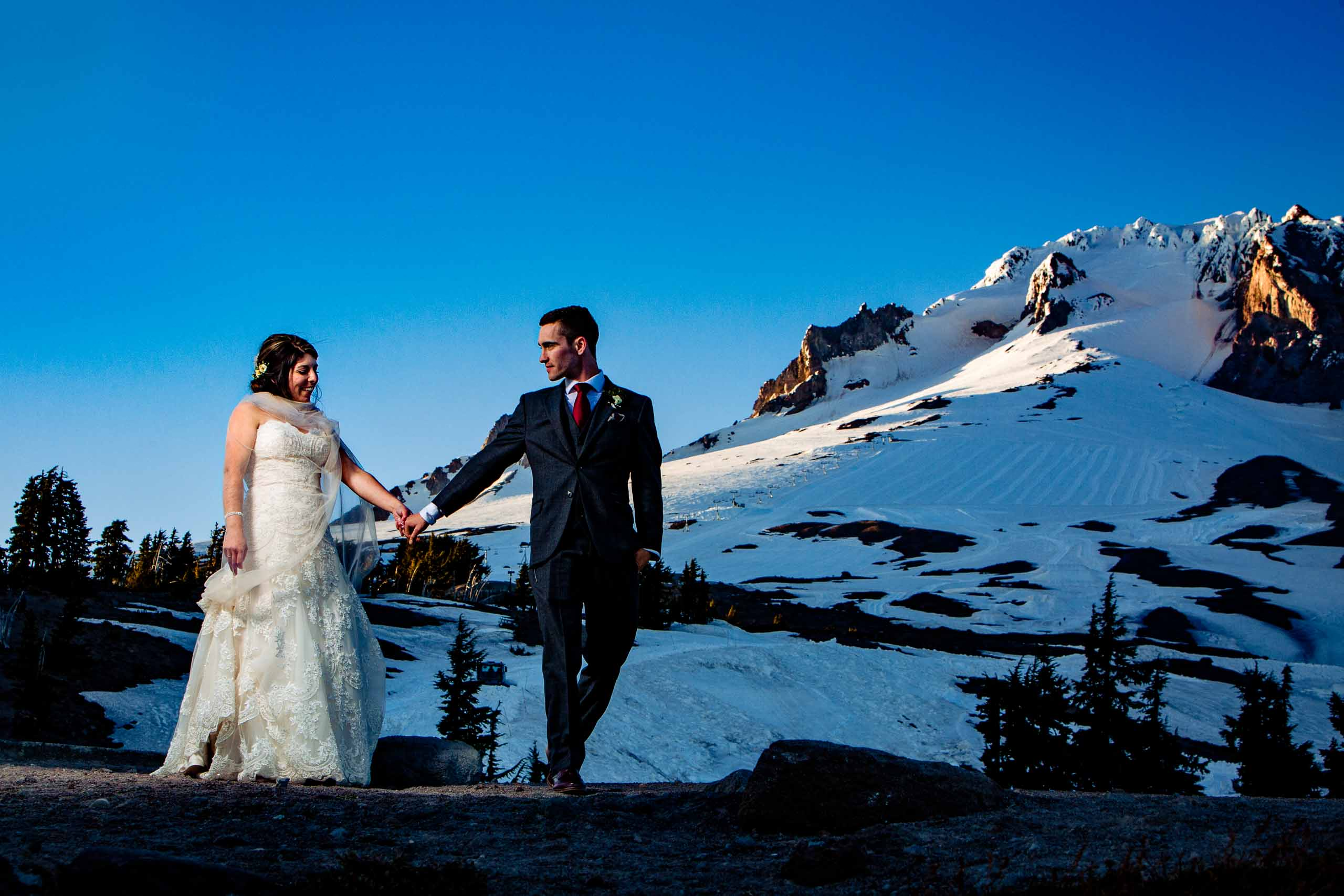 Bride and groom walking together with Mt Hood in the background moments after their Timberline Lodge Wedding ceremony