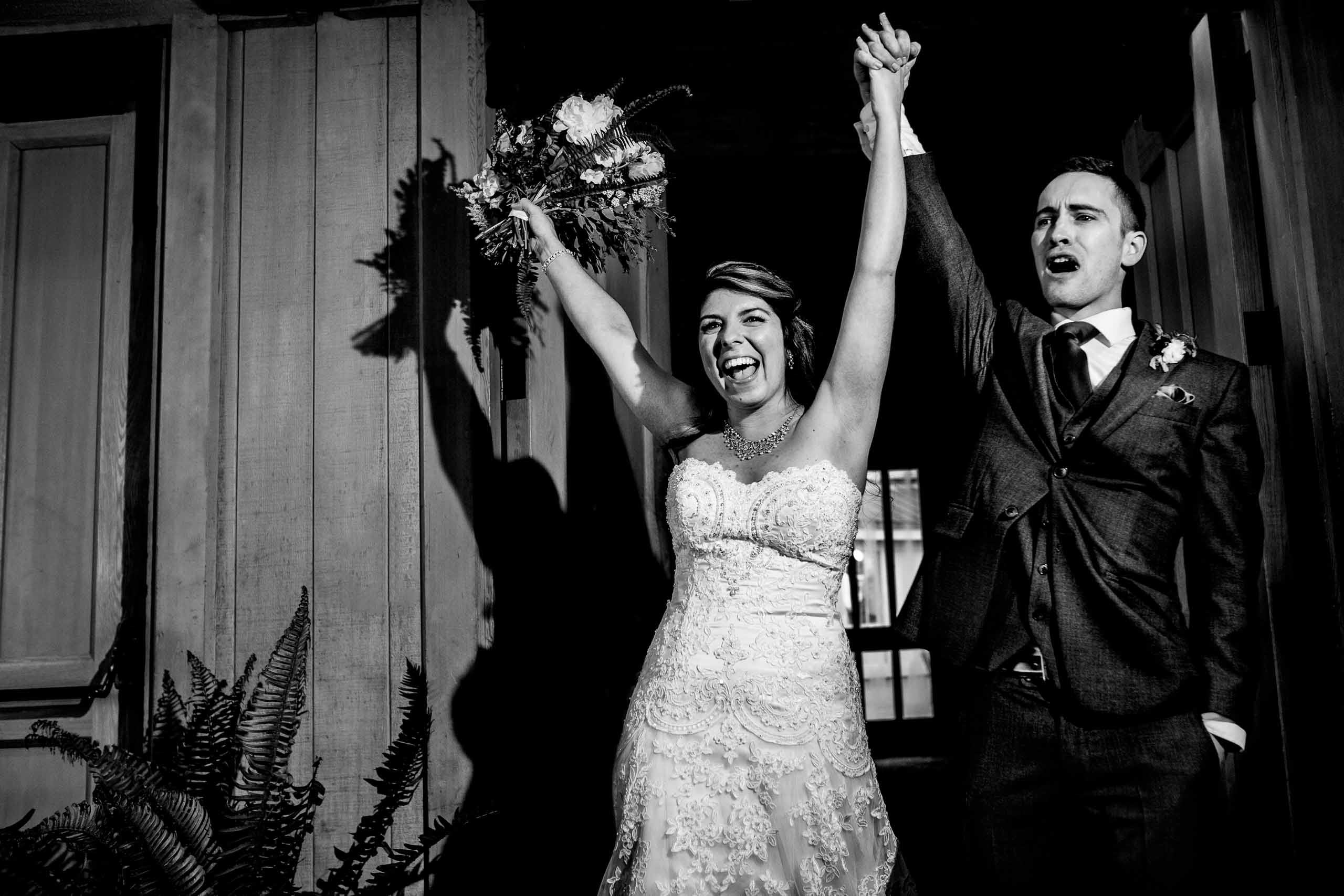 Bride and groom entering their Timberline Lodge Wedding reception with hands up while laughing with joy