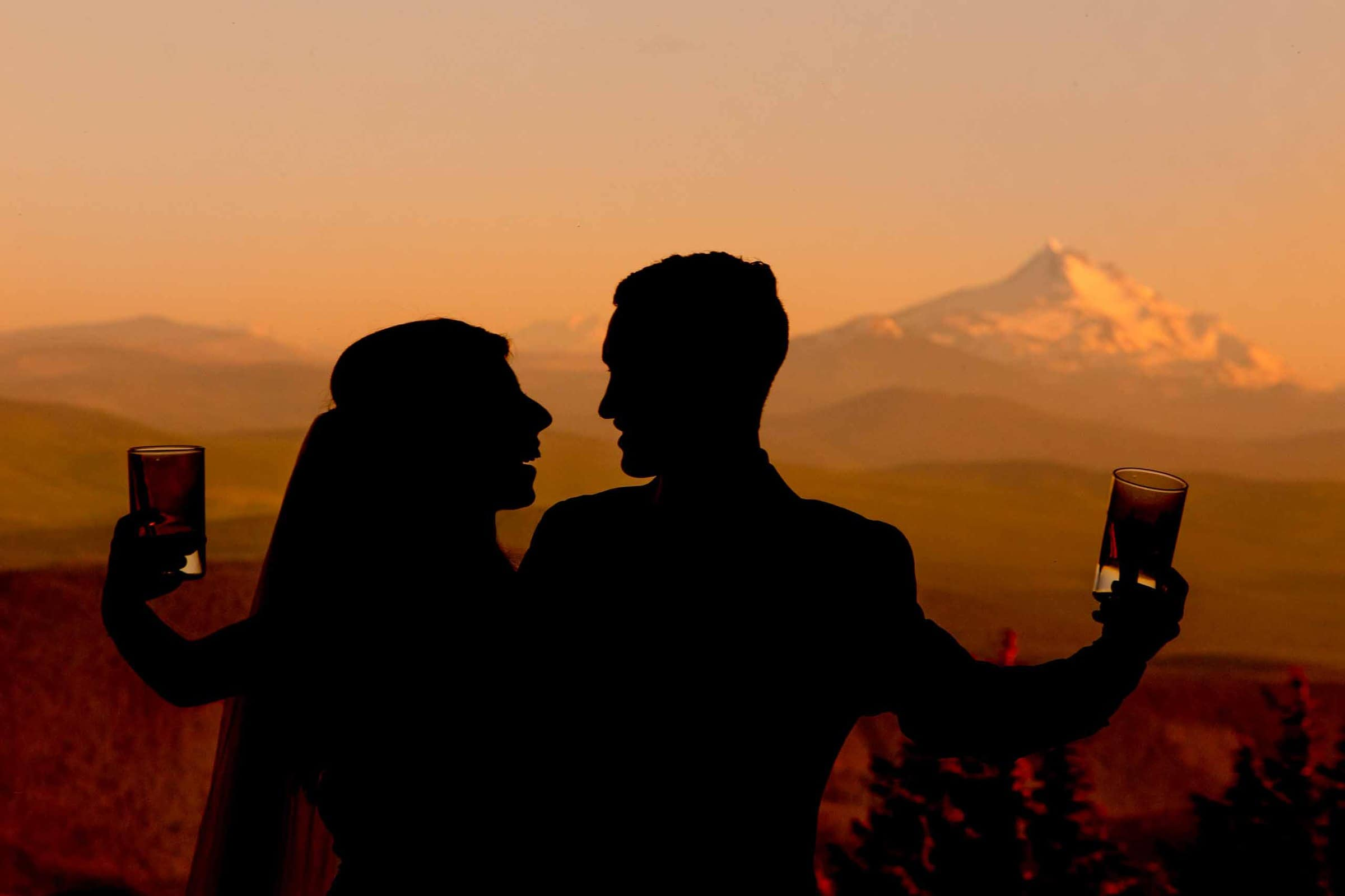 Bride and groom holding champagne glasses up at sunset with golden light behind them during their Timberline Lodge Wedding reception