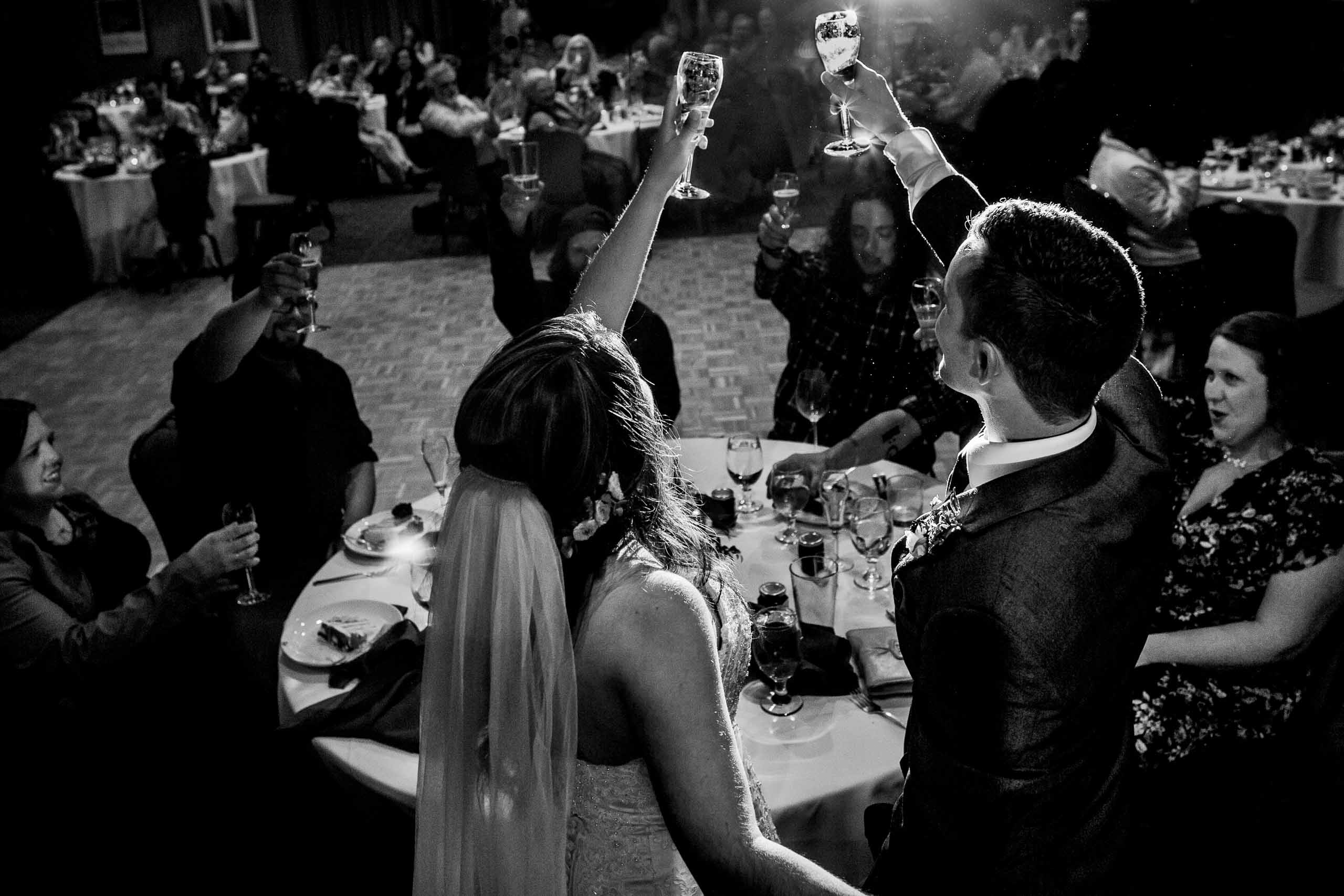 Bride and groom raising champagne glasses during their Timberline Lodge Wedding reception