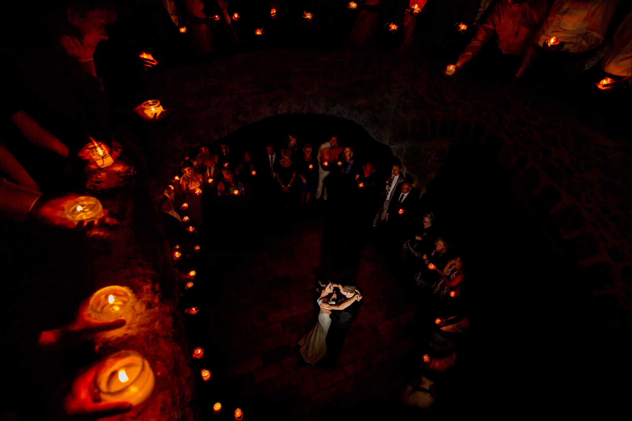 Award winning photo of bride and groom first dance surrounded by guests holding candles in a French Chateau south of france
