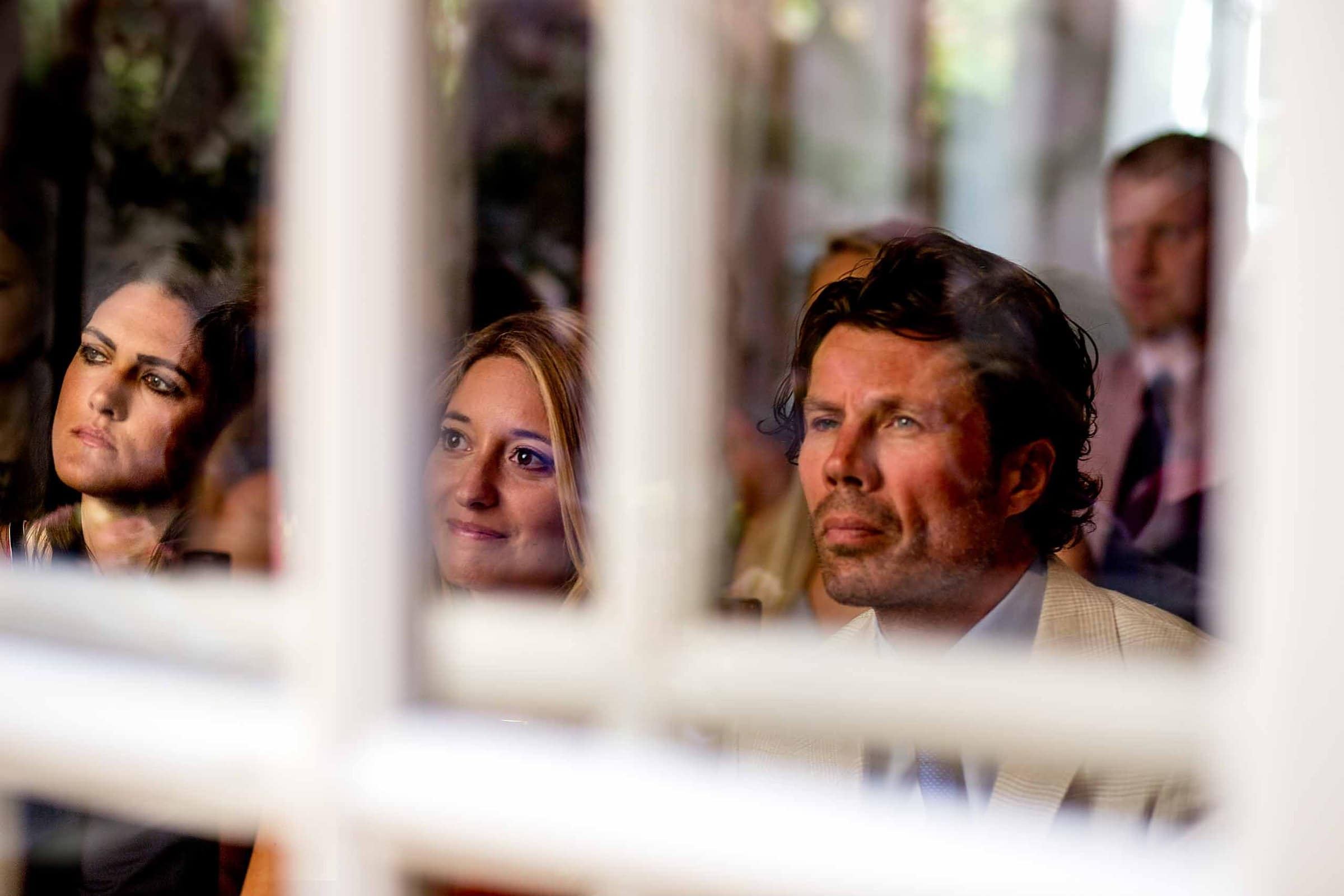 Guests looking through a back window in on a Chateau Zen wedding ceremony in the South of France near Montepelier.