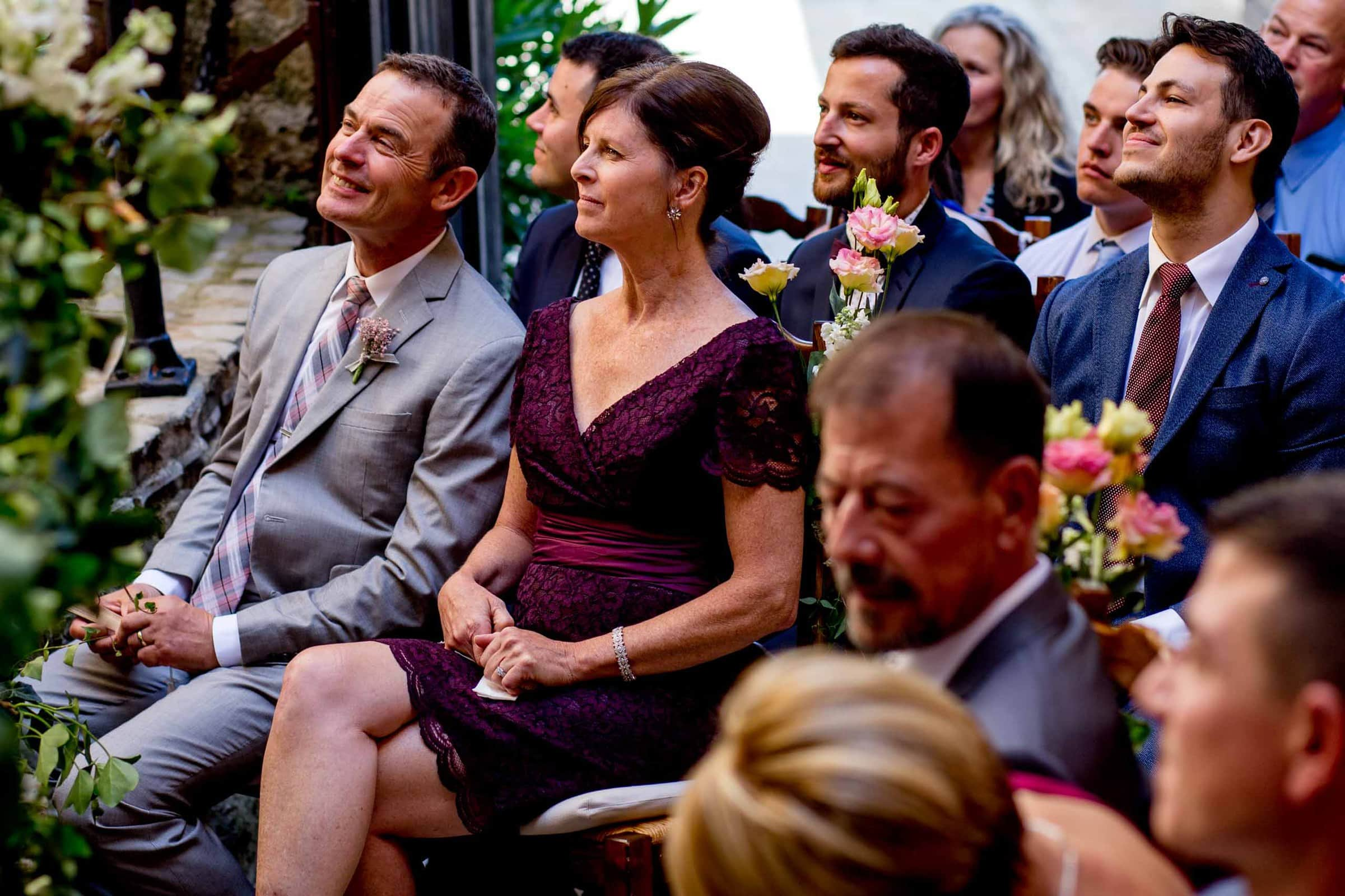 Parents of the bride seated during a Chateau Zen wedding ceremony in the South of France near Montepelier.