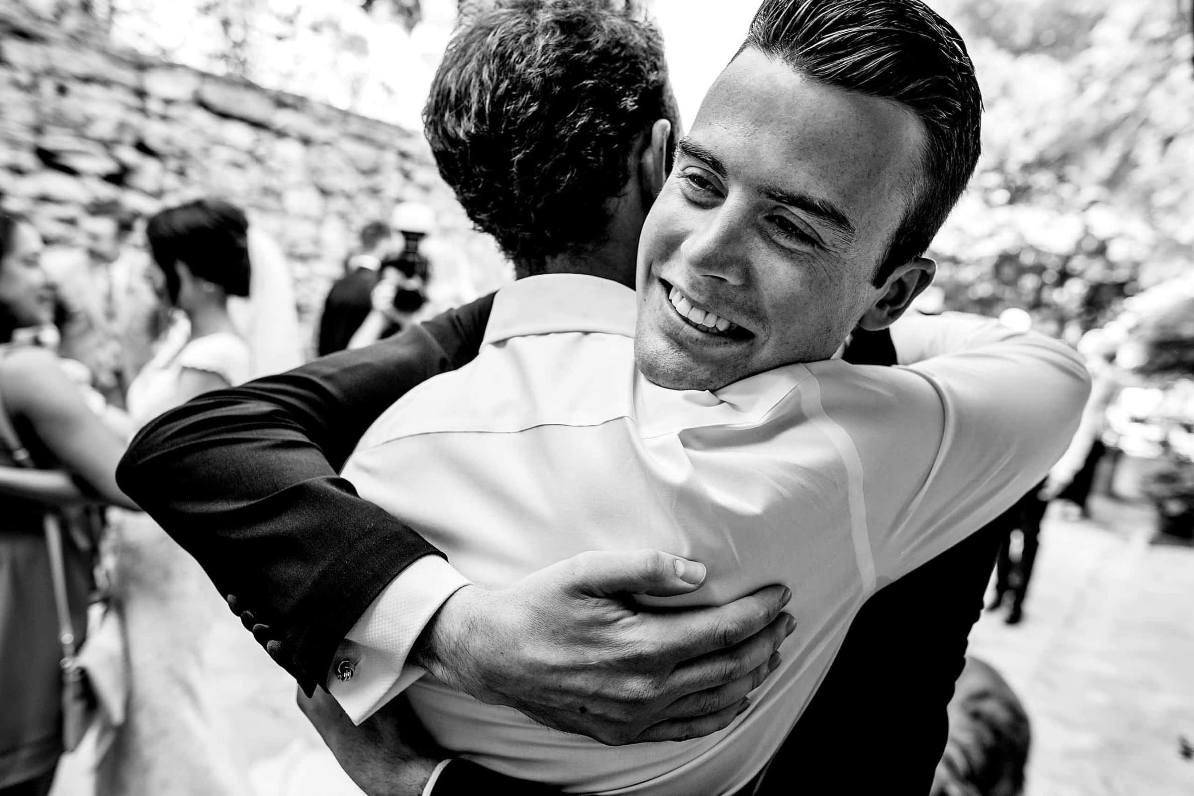 Emotional photo of a groom hugging his best friend during a Chateau Zen wedding in the south of France near Montpelier.