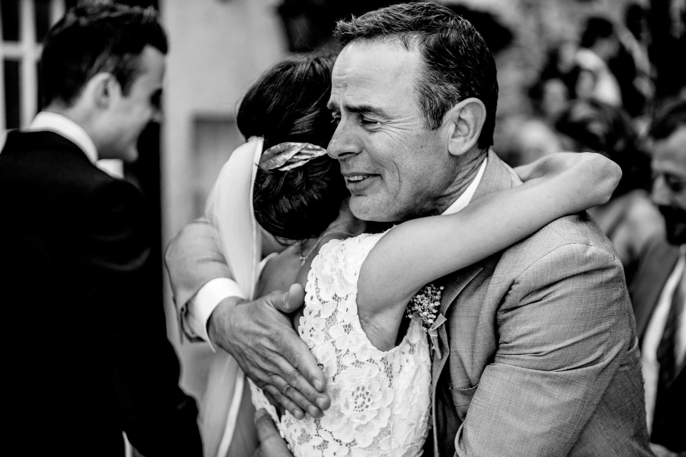 Emotional photo of a father hugging a bride during a Chateau Zen wedding in the south of France near Montpelier.