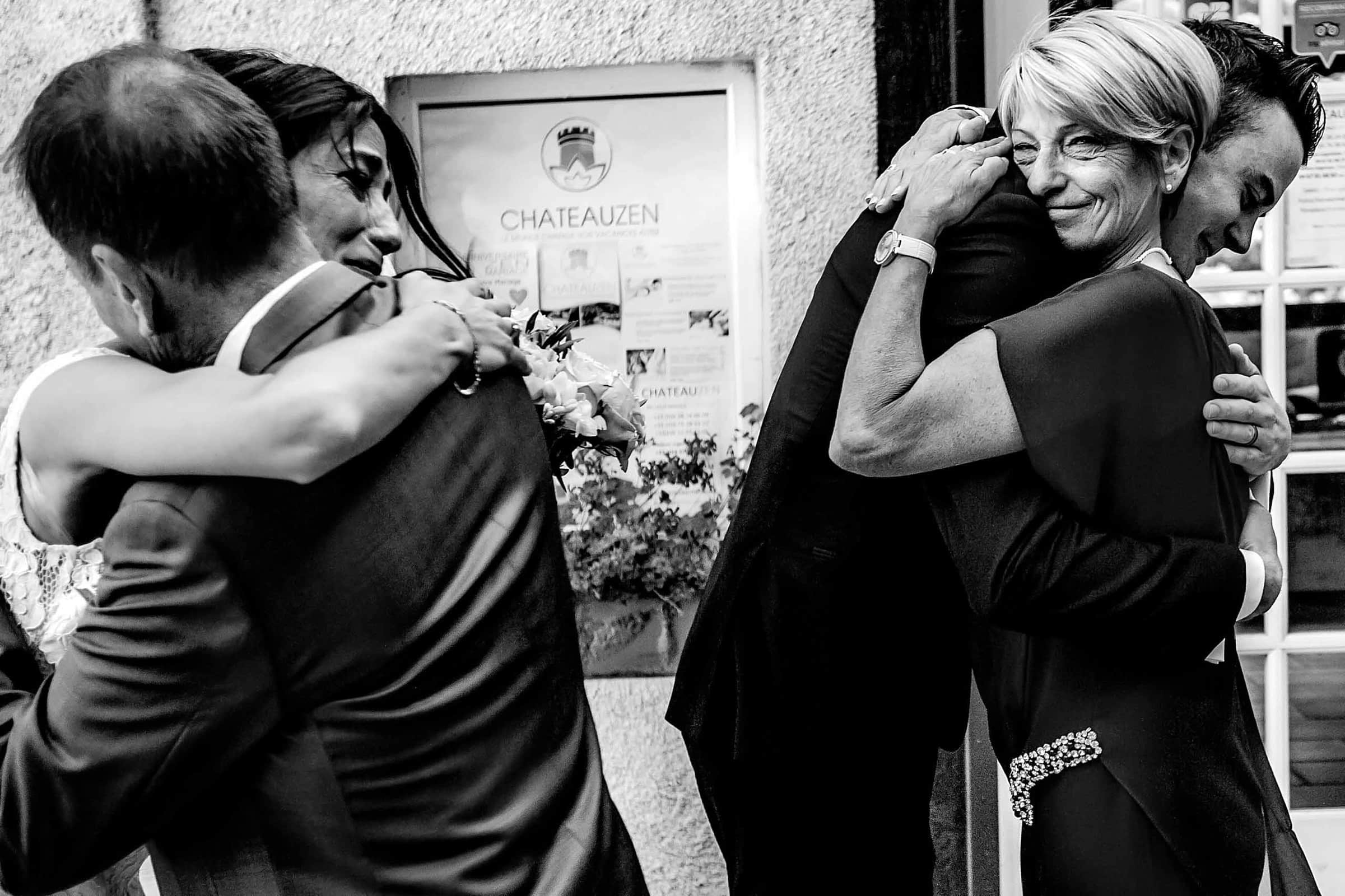 Emotional photo of parents hugging a bride and groom during a Chateau Zen wedding in the south of France near Montpelier.