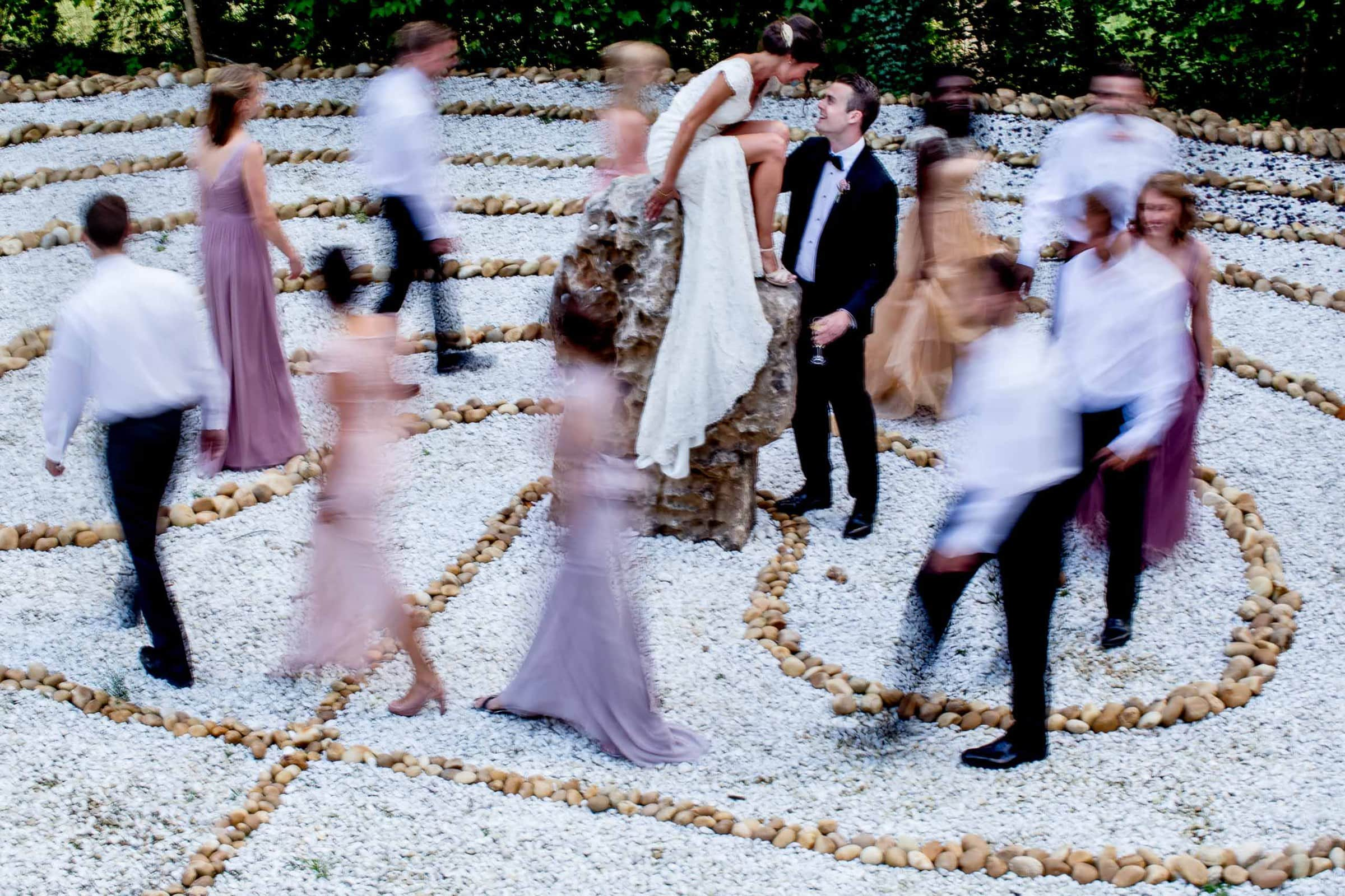 Friends circling in a blur around bride and groom in Cirque de Navacelles valley during their Chateau Zen wedding in the South of France near Montepelier.