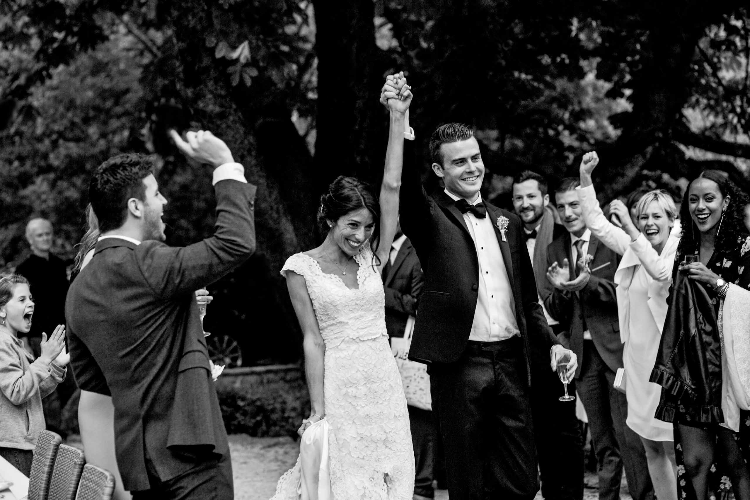 Bride and groom entering their Chateau Zen wedding reception with family and friends cheering them on in the South of France.