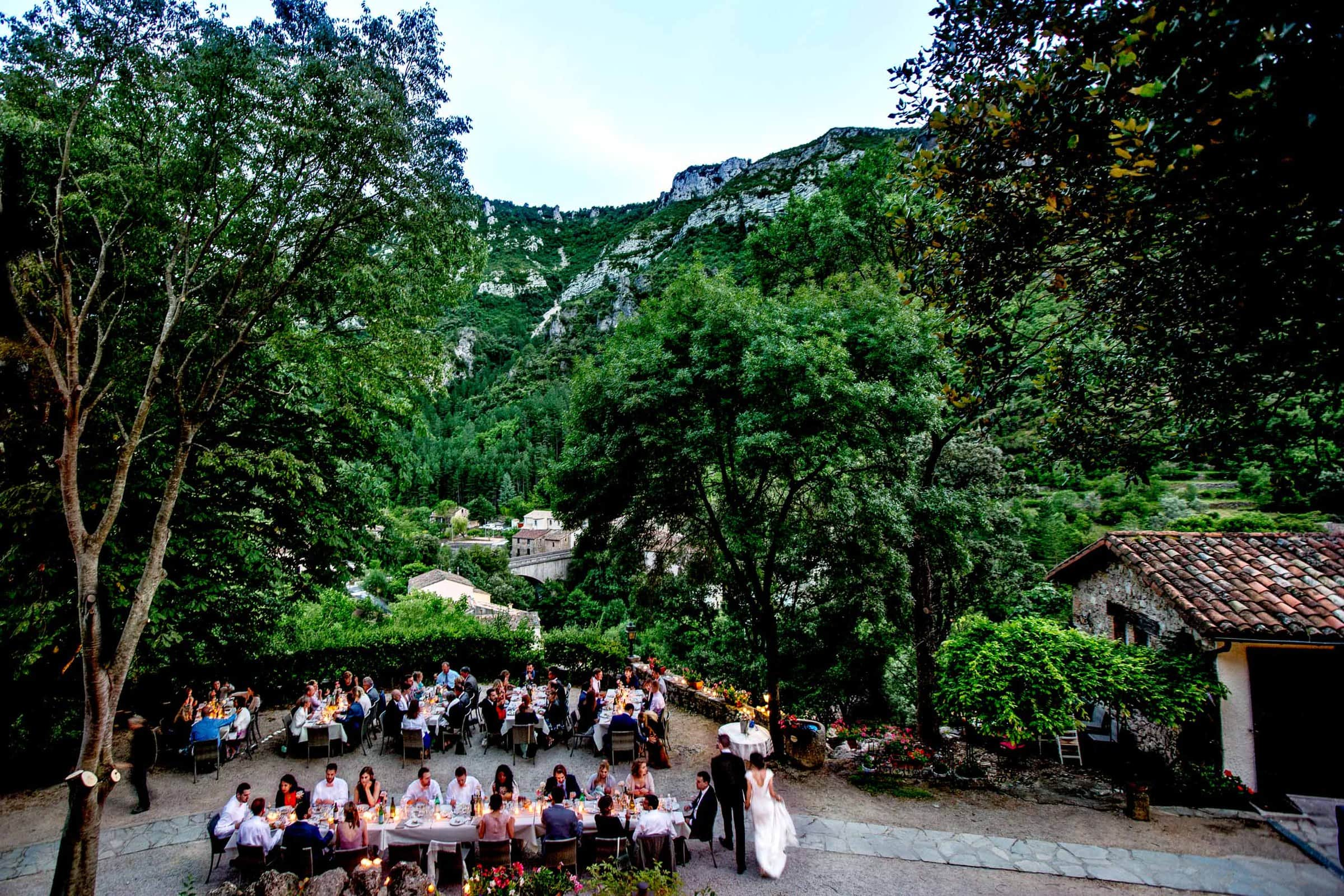 Bride and groom walking around their Chateau Zen wedding reception with family and friends at a long dinner table in the South of France.