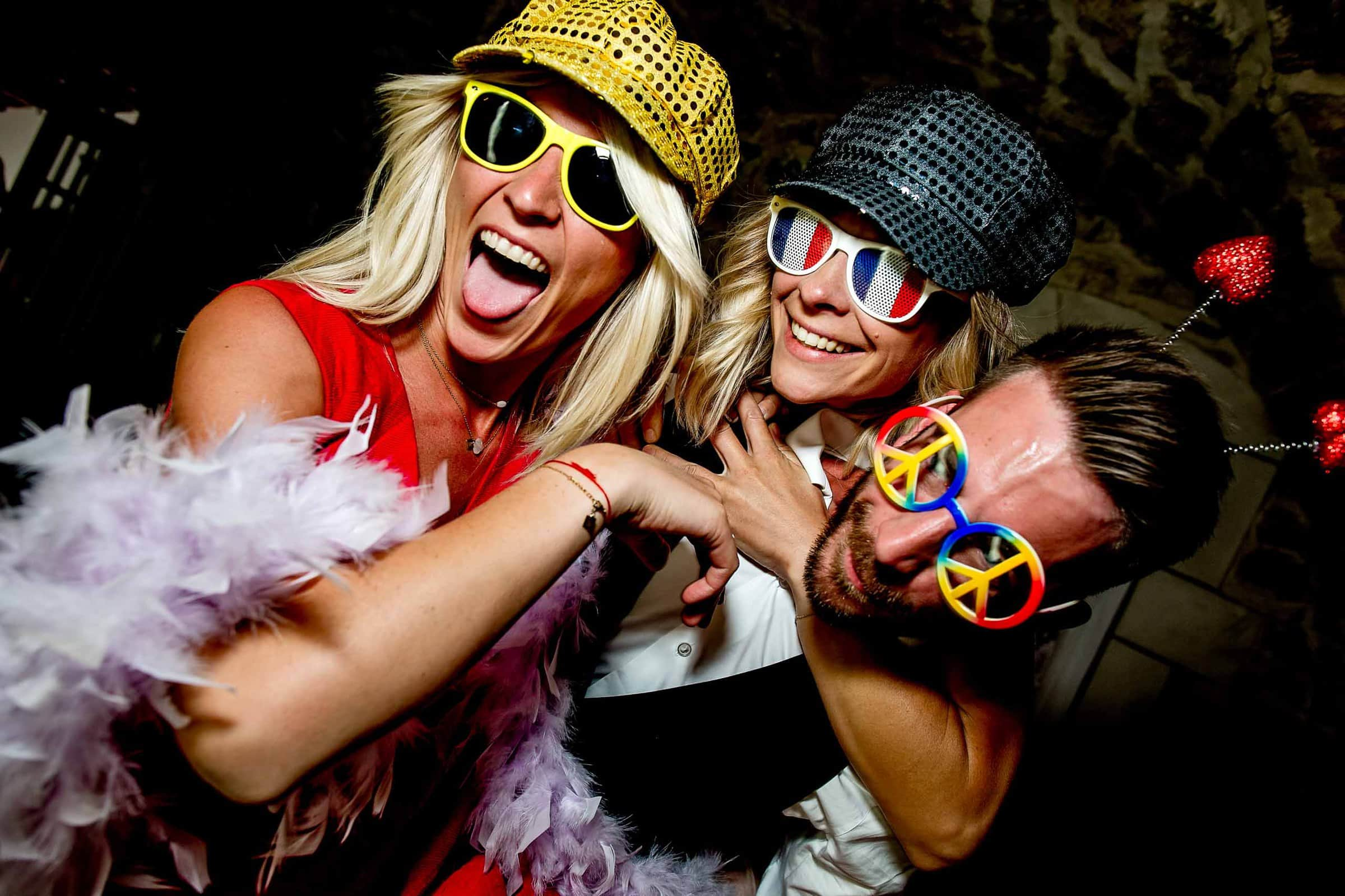 Fun crazy party guests with fun hats and sunglasses during a Chateau Zen wedding reception
