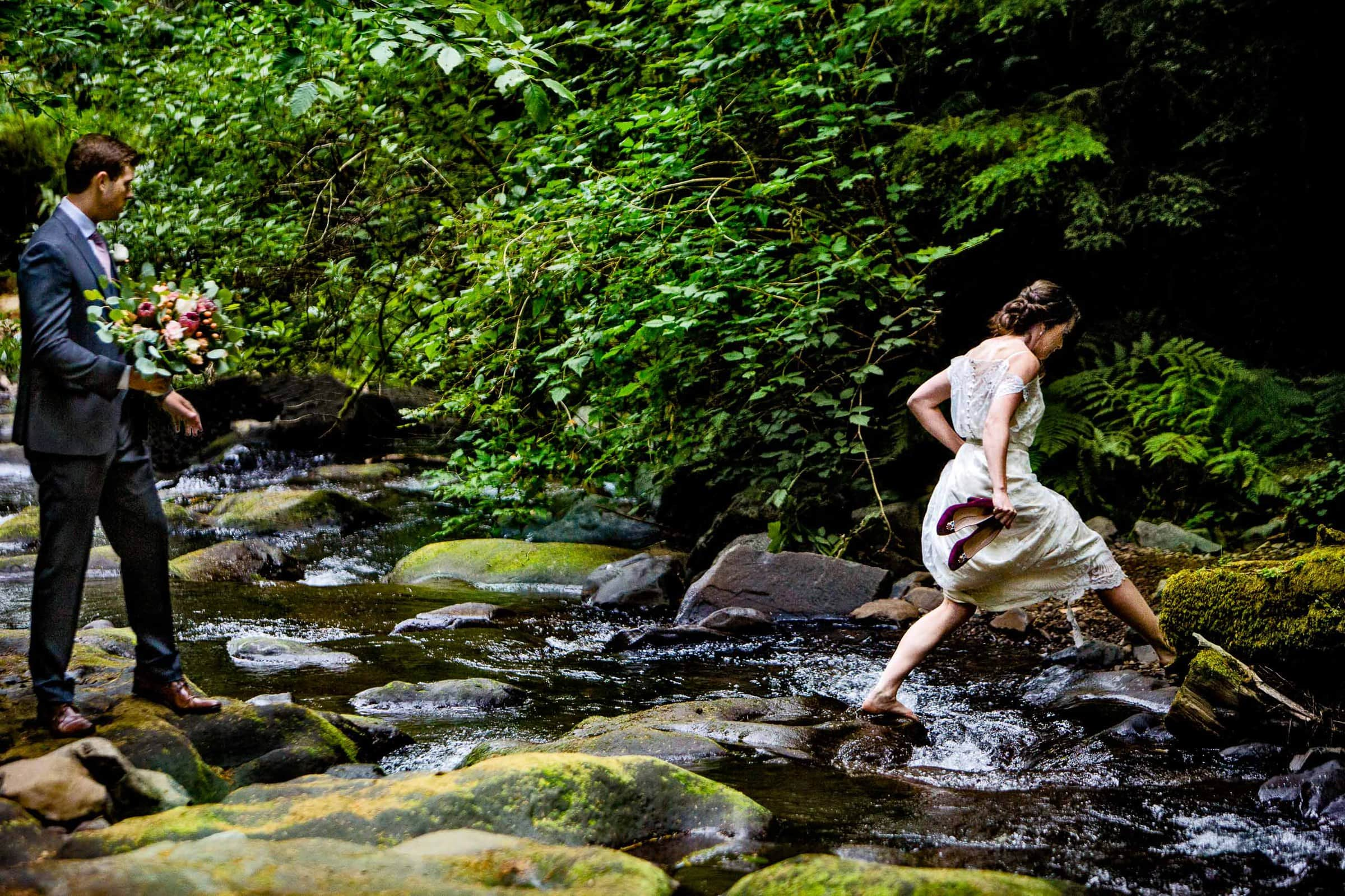 Bride walking across a river for her Oregon Coast Elopement