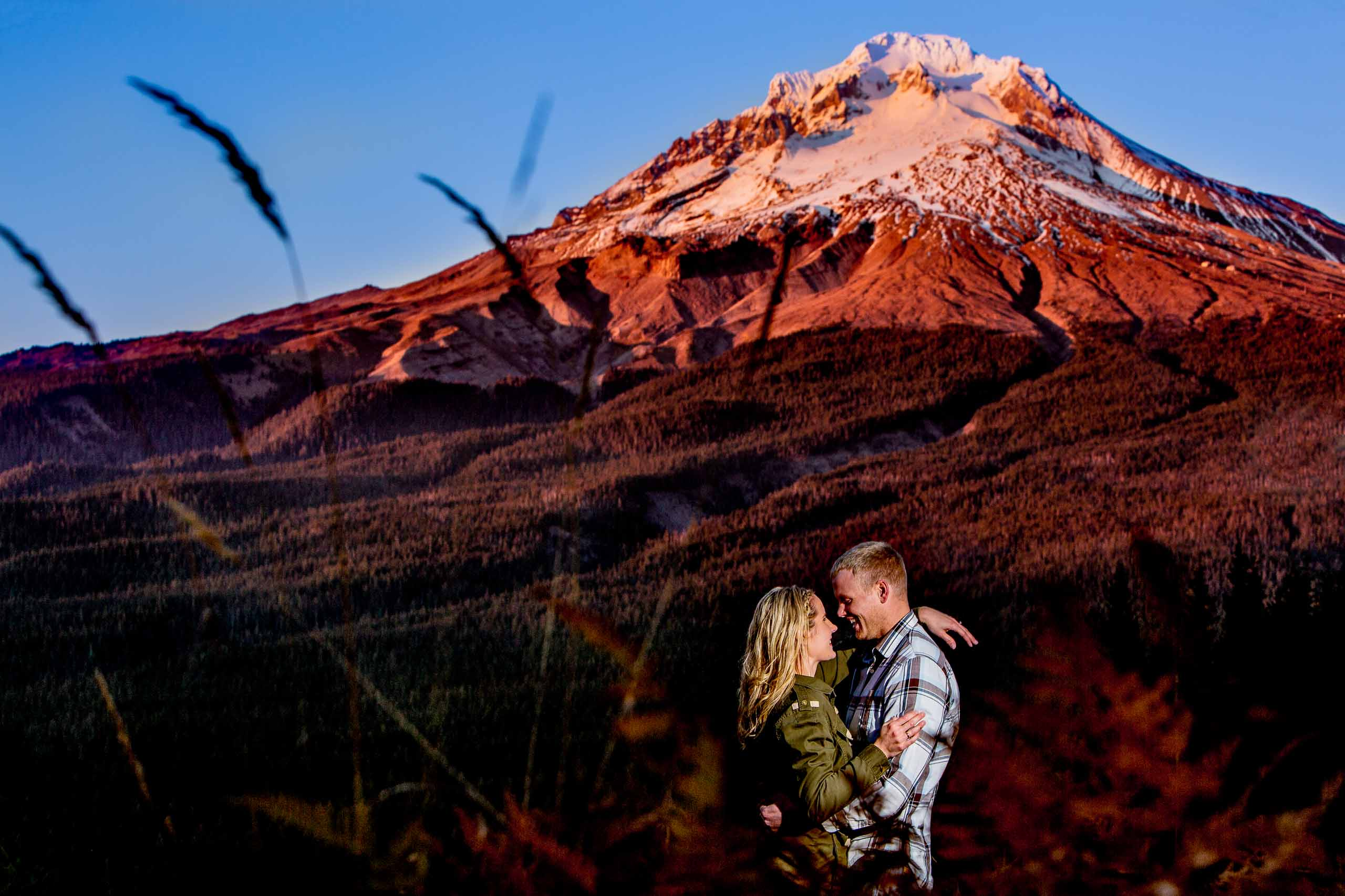 A vast view of Mt Hood with a couple embracing during their Mt Hood engagement photos