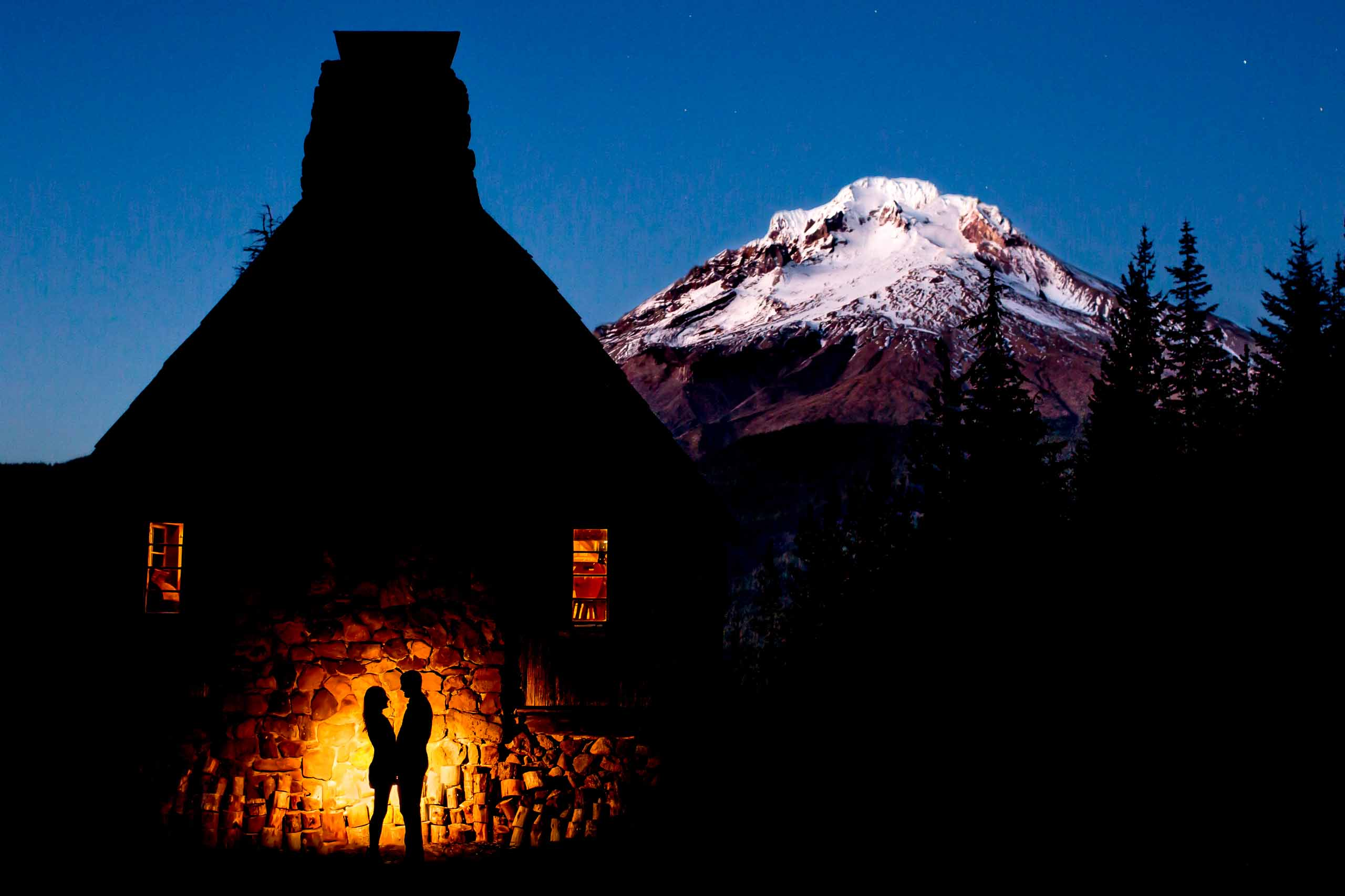 A stunning silhouette of a couple at a warming hut during their Mt Hood engagement photos