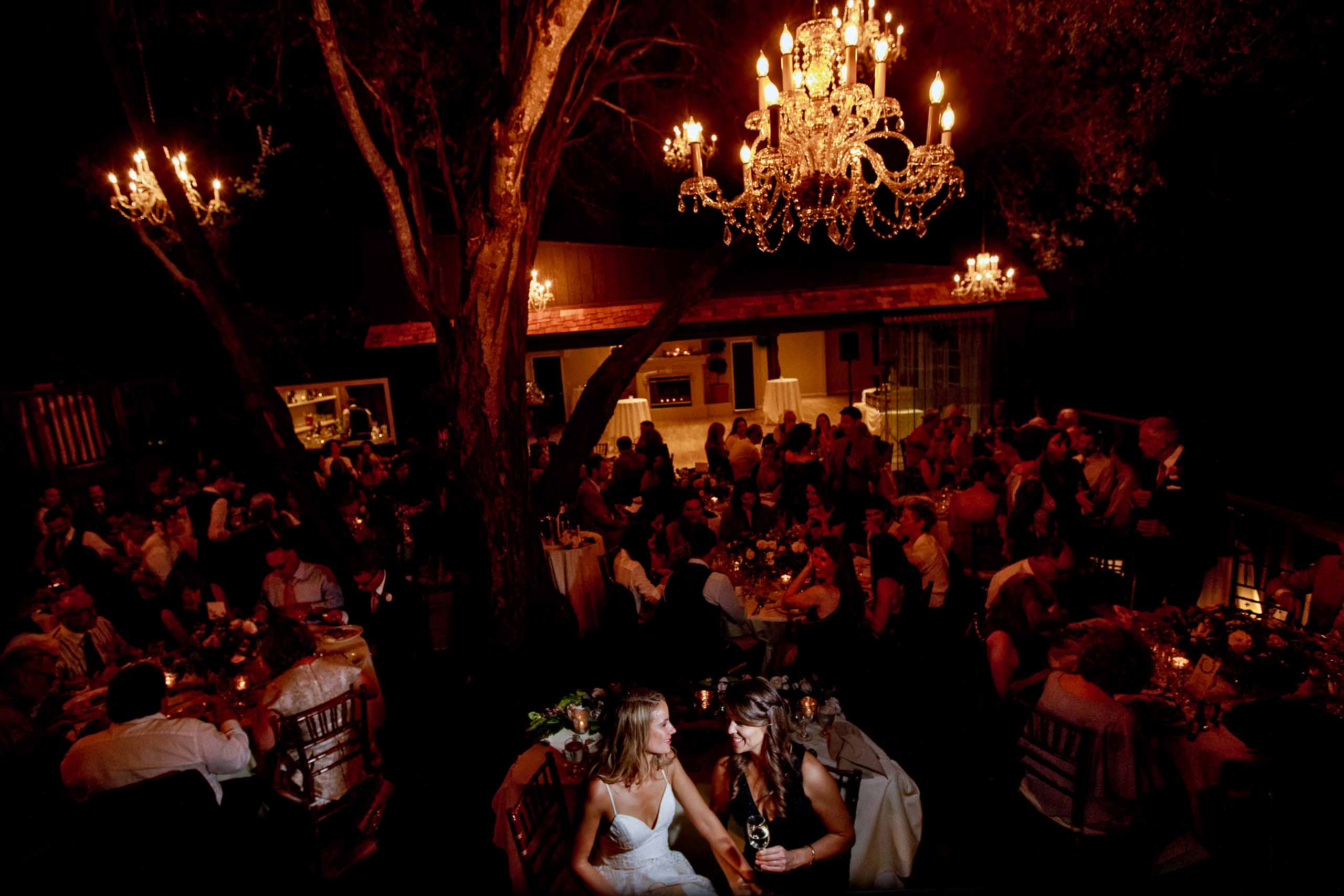 Two brides enjoying their Calamigos Ranch Wedding reception under candle light surrounded by friends and family in Malibu, California