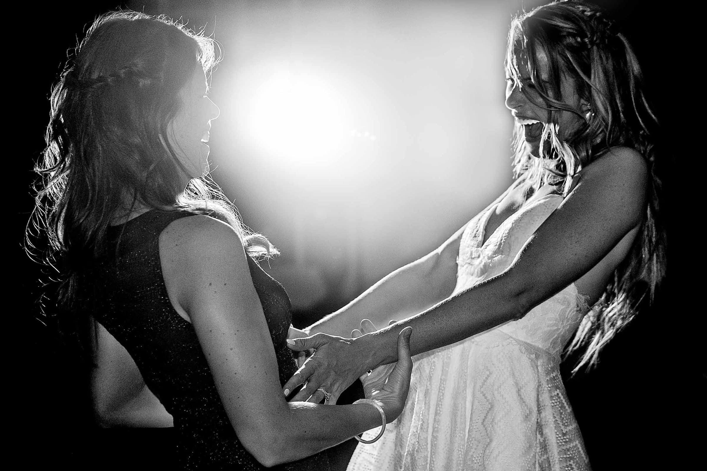 Two happy brides ecstatic dancing during their Calamigos Ranch Wedding in Malibu, California