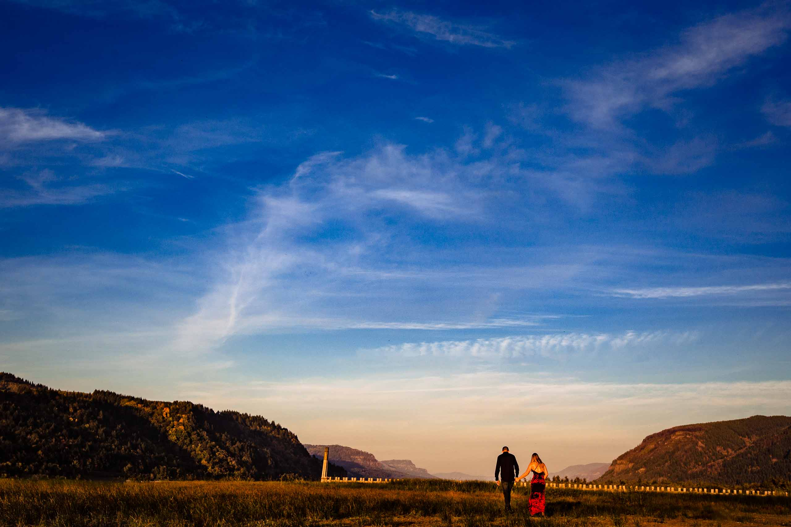 An intimate Columbia Gorge engagement photo of a couple walking together at sunset just outside Hood River Oregon