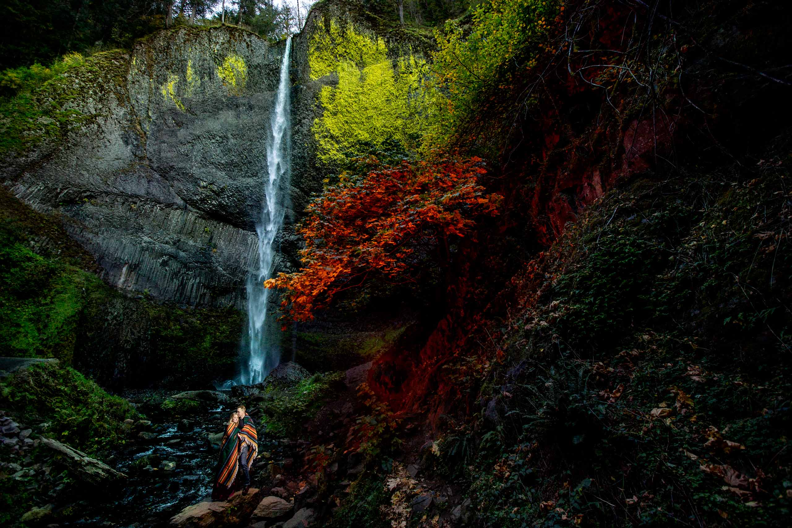 A lovely Columbia Gorge engagement photo of a couple snuggling near a colorful waterfall just outside Hood River Oregon