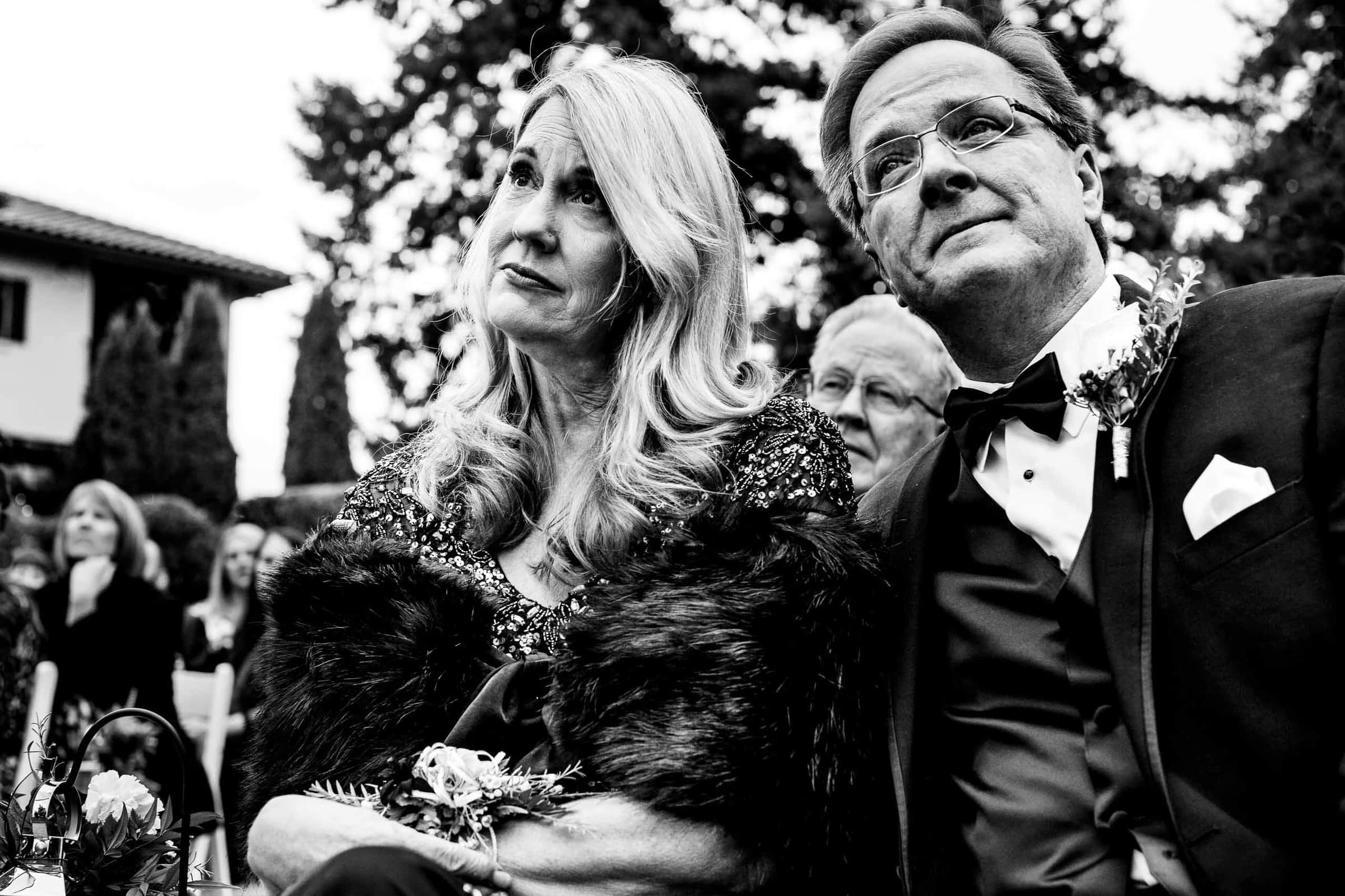 Emotional parents listening to a bride and groom exchanging vows during their Columbia Gorge Hotel wedding ceremony