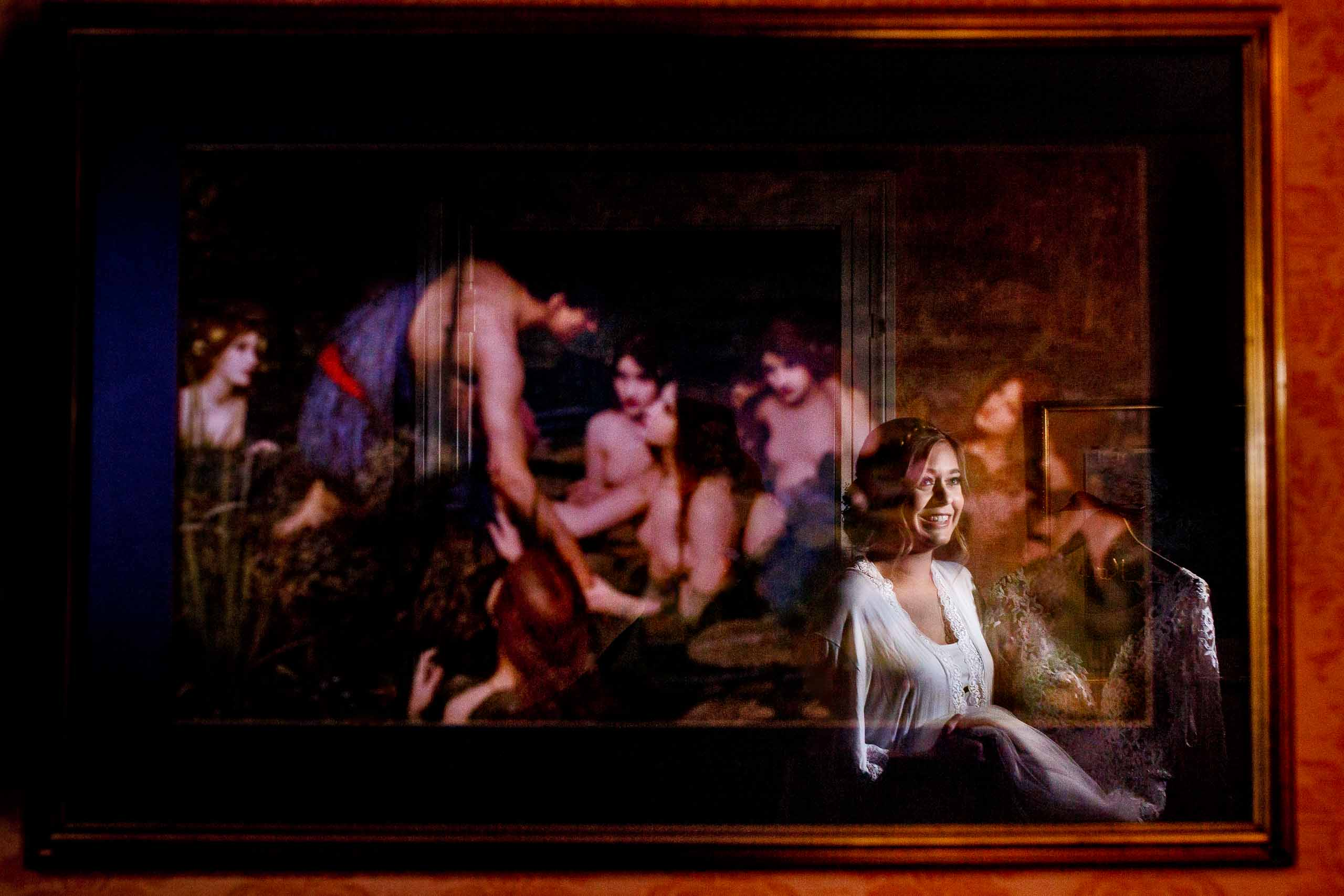 Bride getting ready for her Columbia Gorge Hotel wedding with her image reflected in paintings.