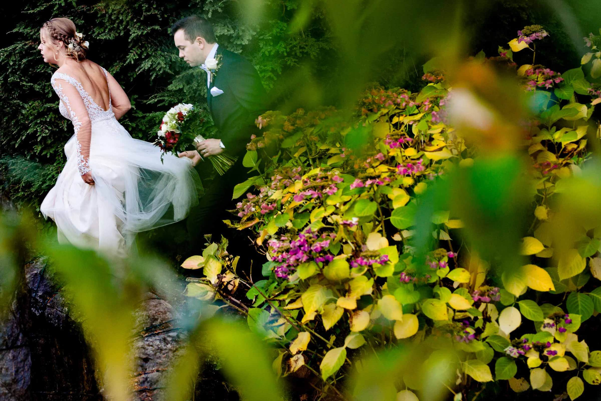 Bride and groom walking through colorful Fall leaves moments just after their Columbia Gorge Hotel wedding ceremony