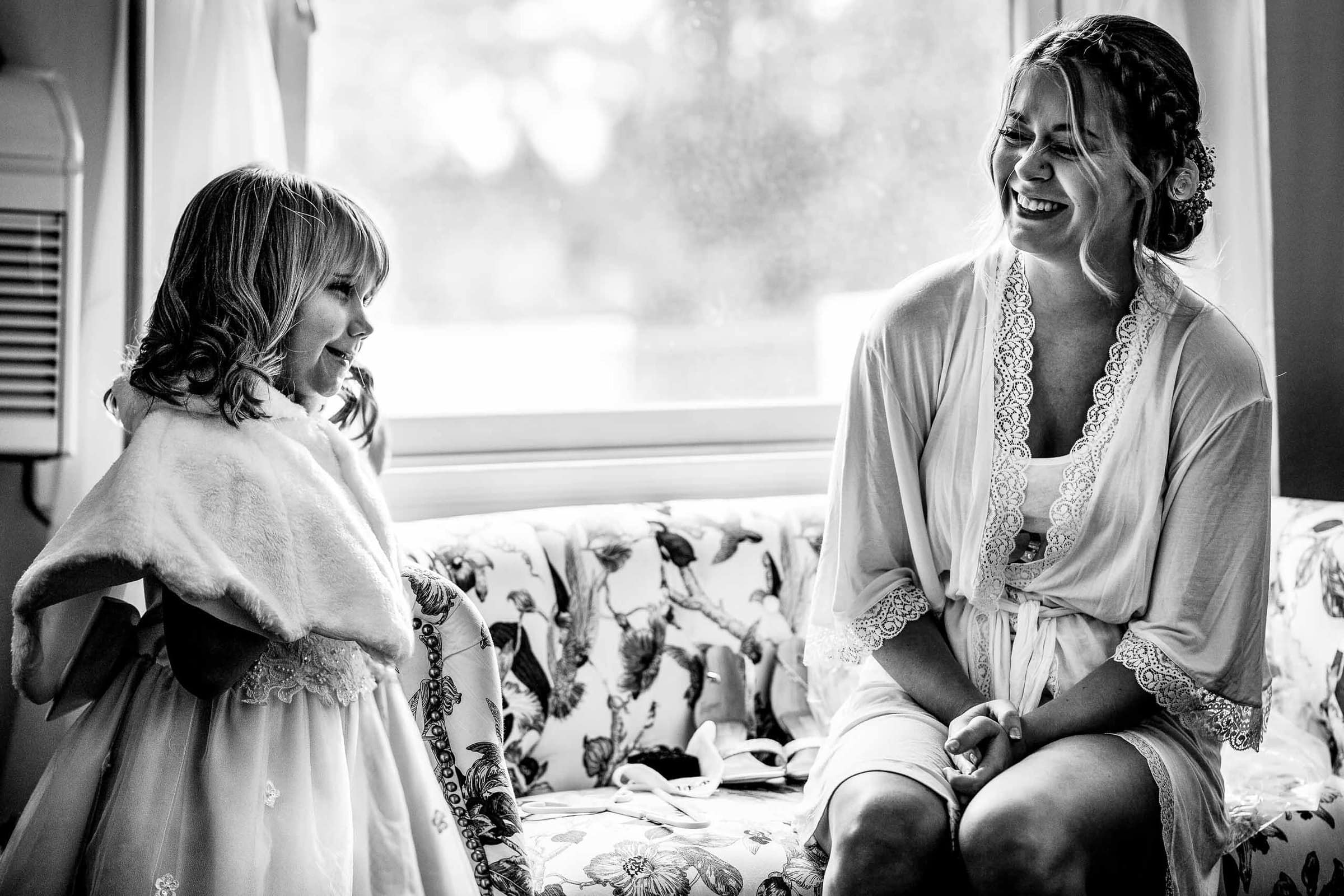 Bride laughing with a young girl before her Columbia Gorge Hotel wedding in Hood River Oregon.