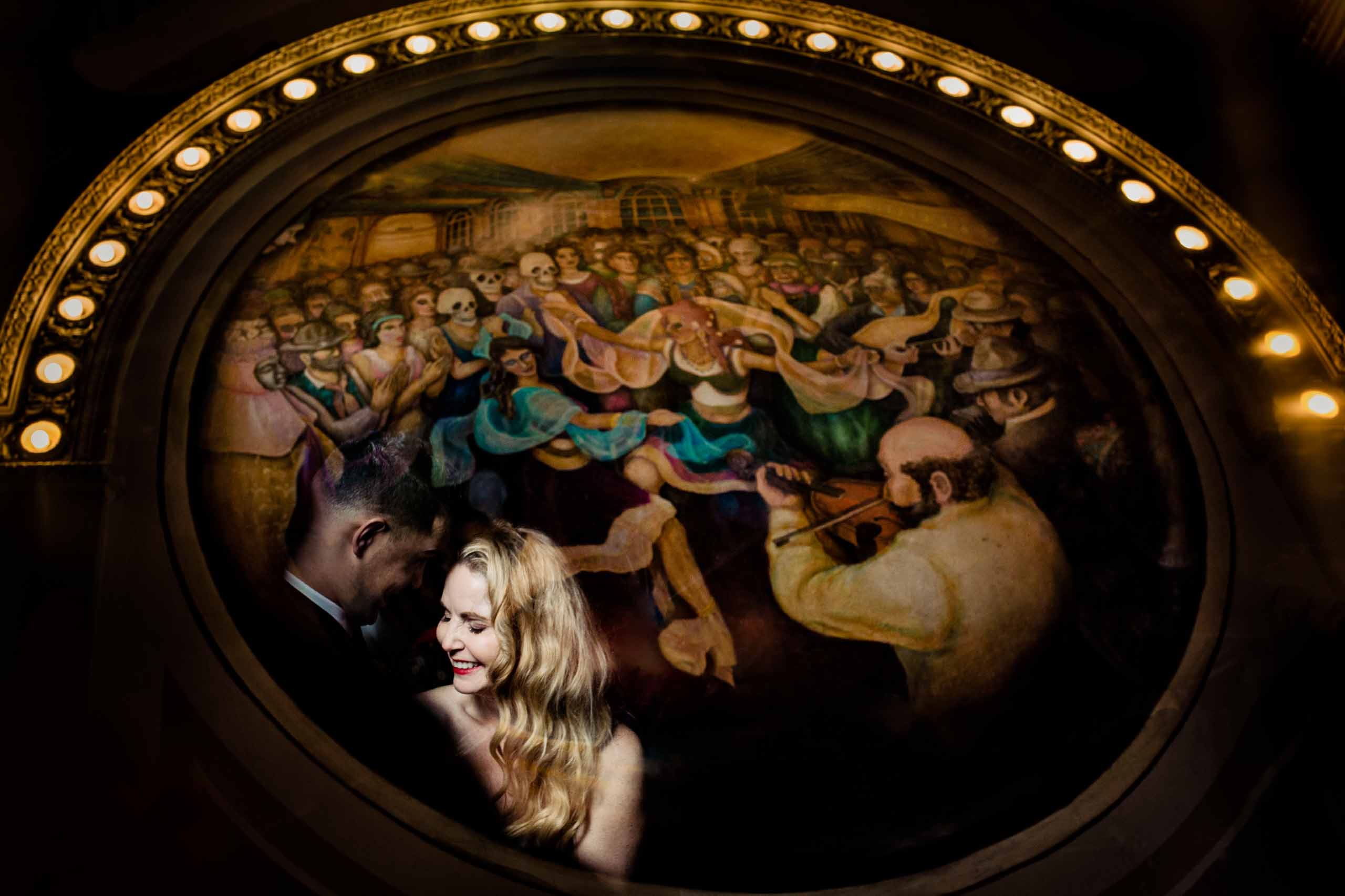Creative photo of bride and groom reflected in a mural painting at the famous Crystal Ballroom in Portland Oregon