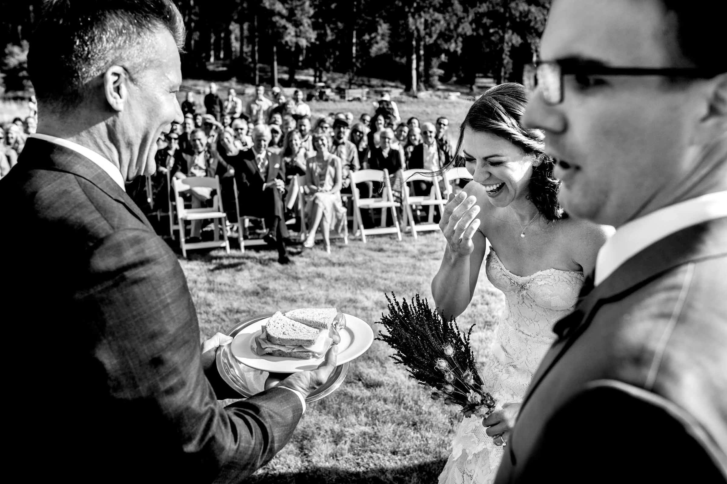 Groom passing a ham sandwhich to his bride during their House on Metolius wedding ceremony