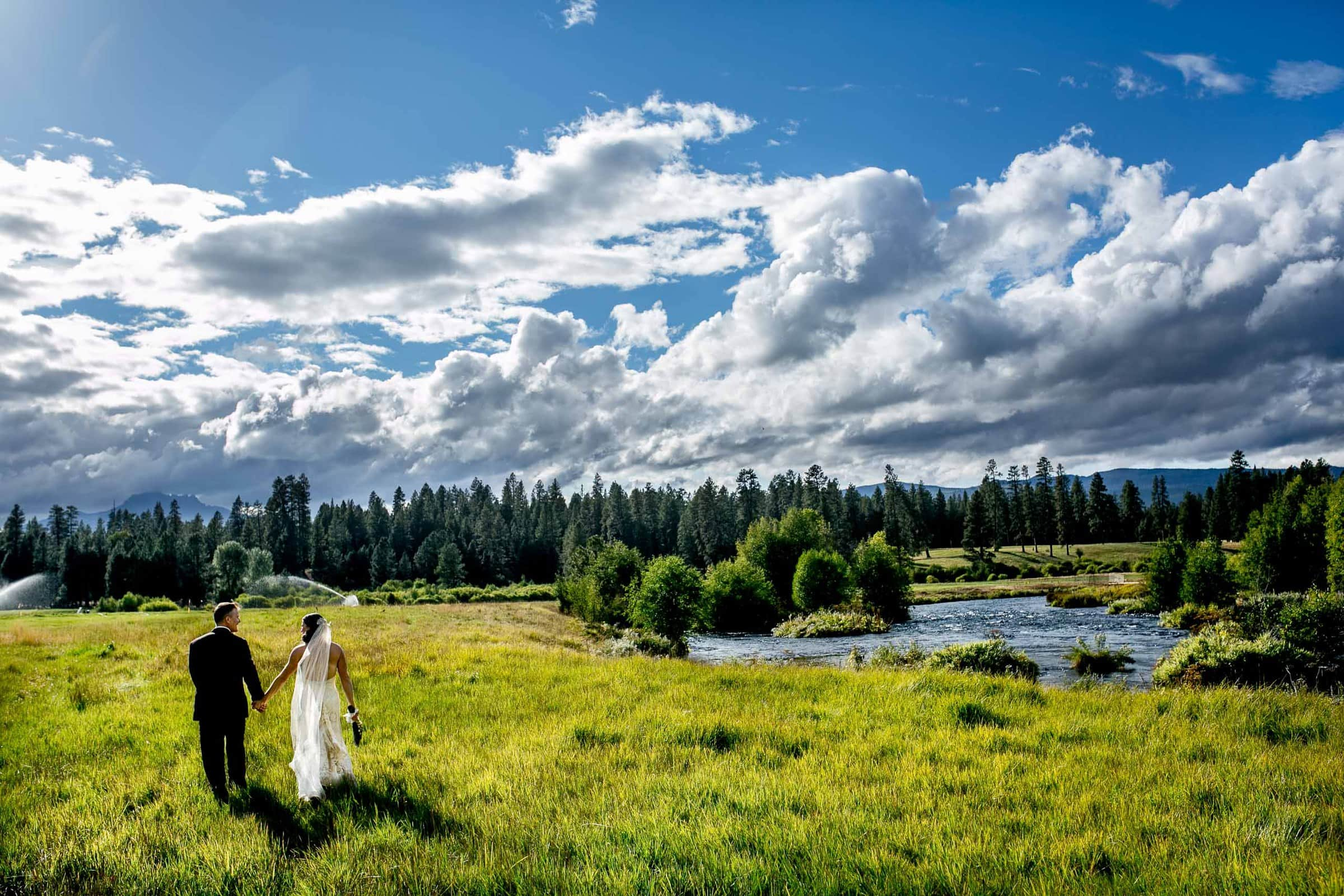 Bride and groom walking along the river for their House on Metolius wedding