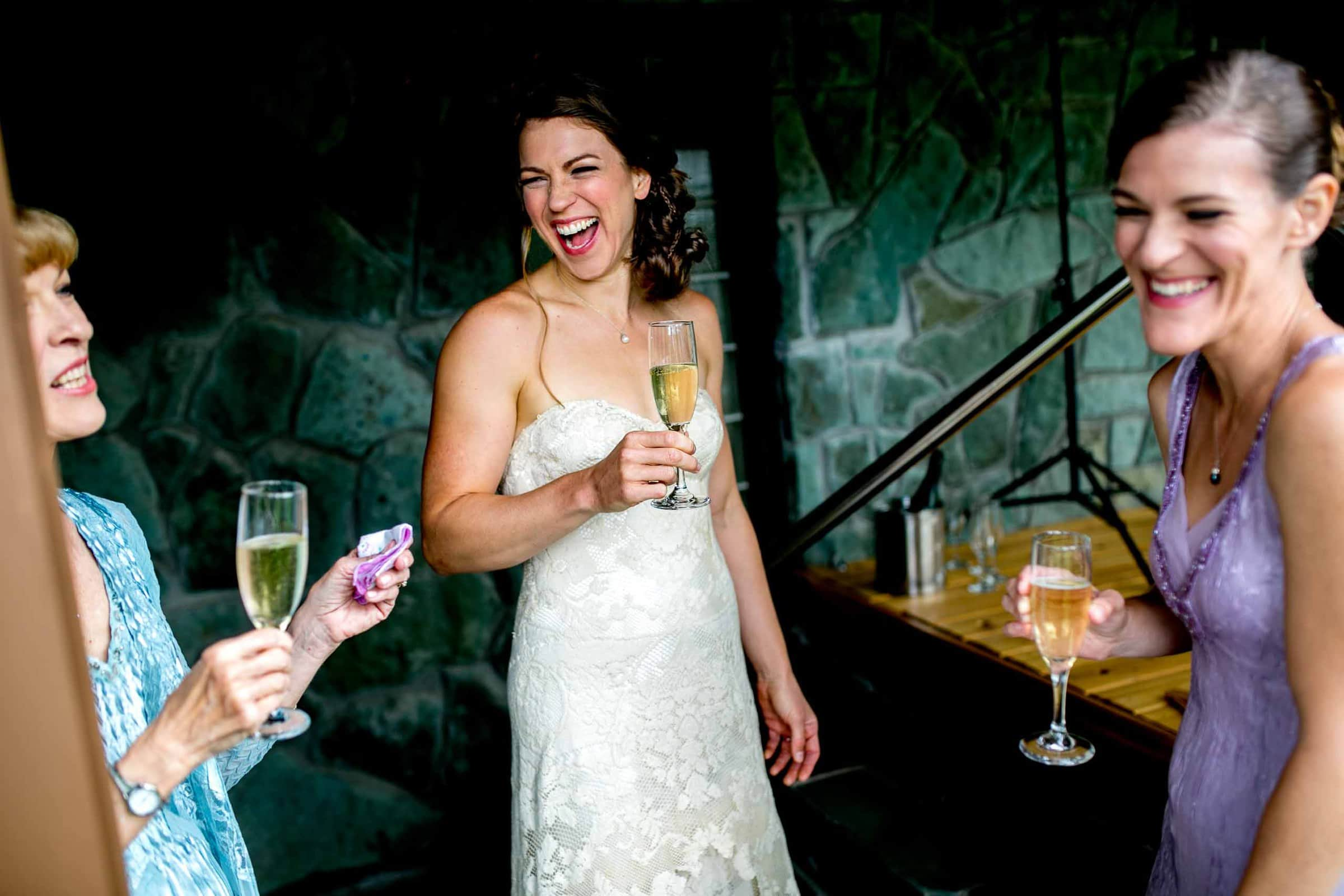 Bride getting ready while laughing with her mother and best friend for her House On Metolius wedding