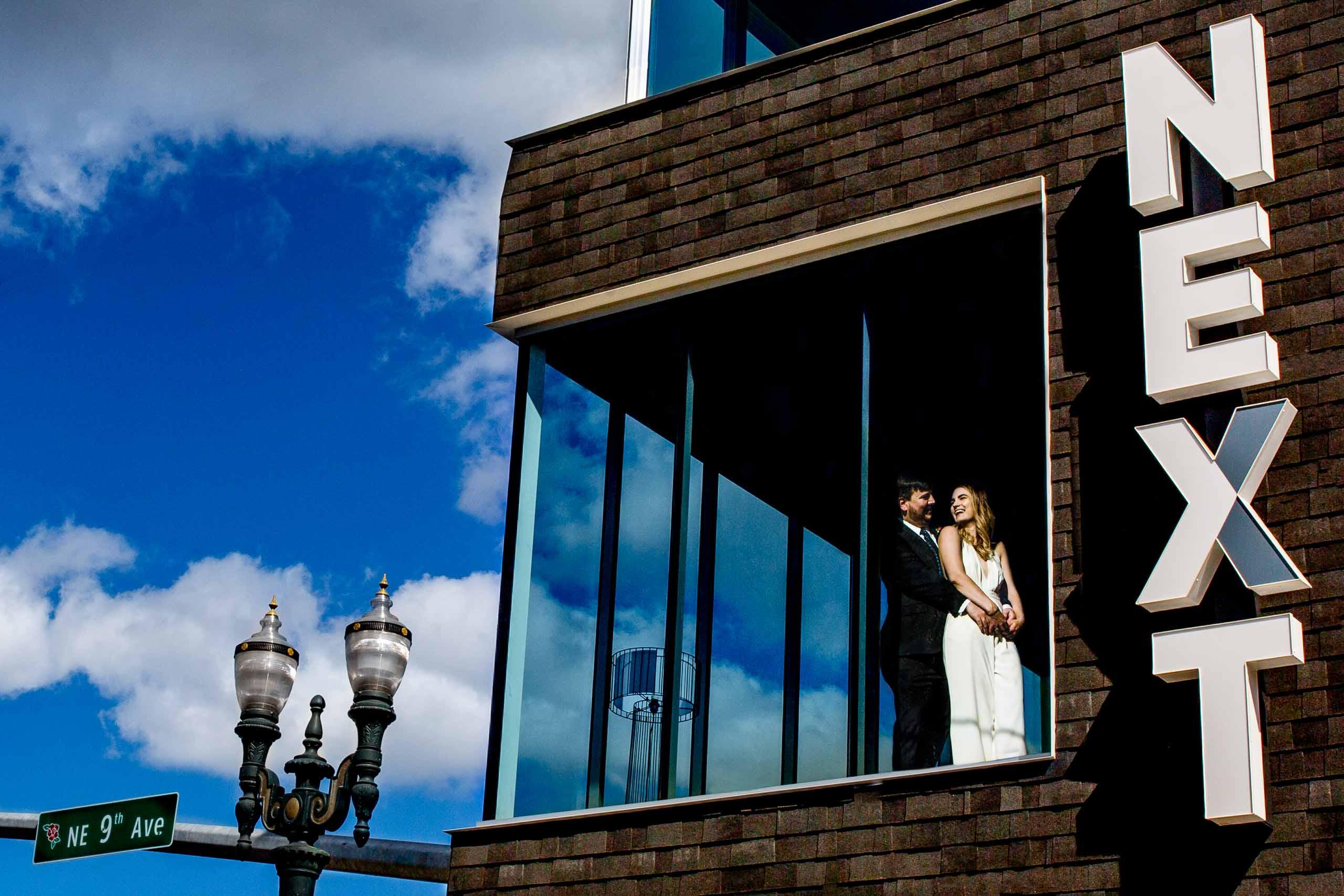Creative bride and groom portrait in a big window during their Jupiter Next wedding