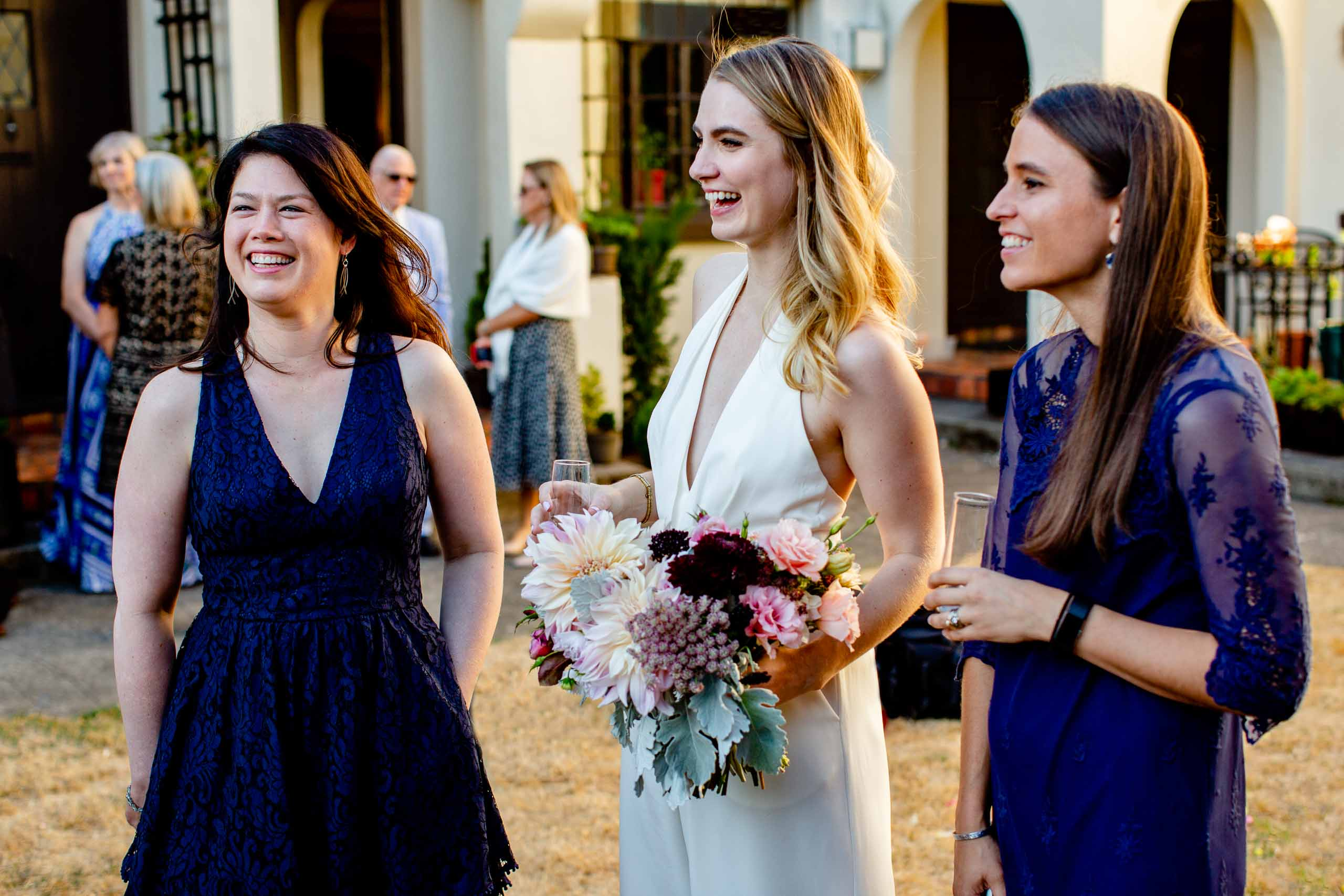 Bride and friends laughing outside in their condo courtyard during their Jupiter Next wedding