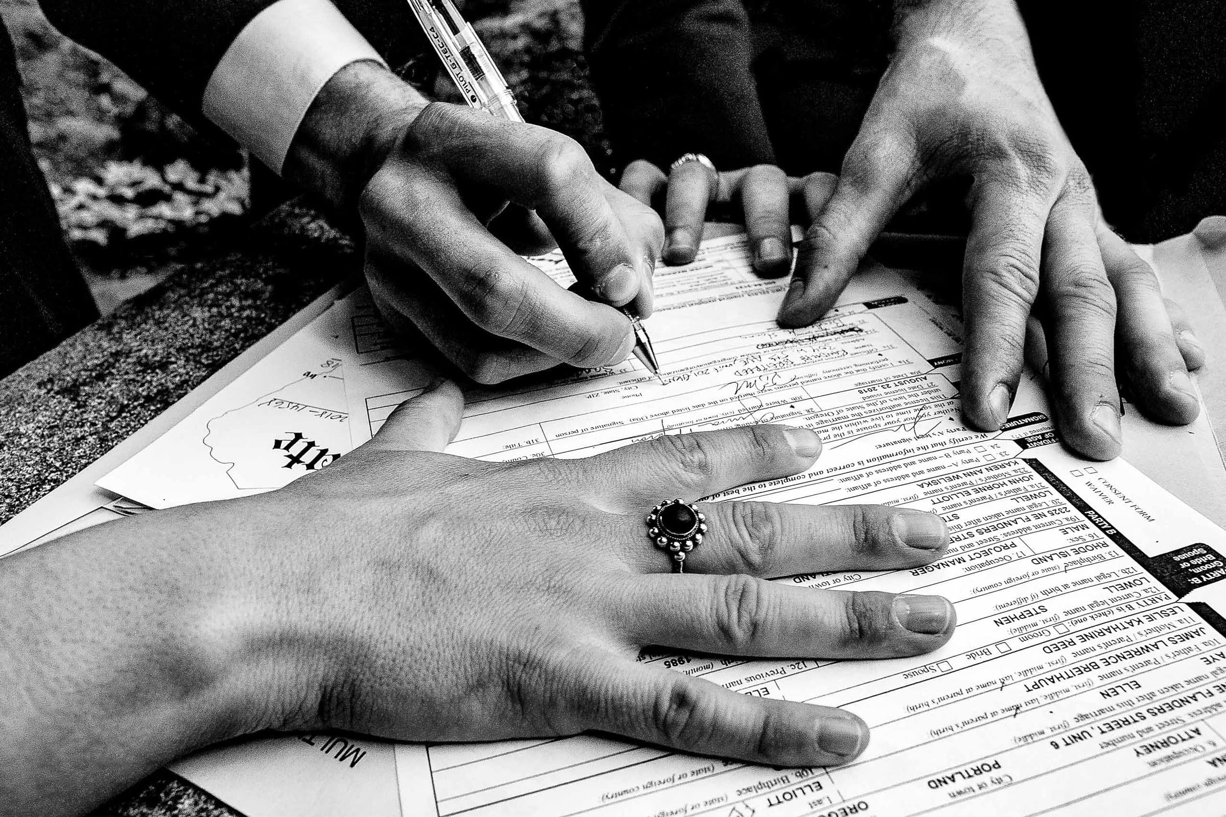 Black and white photo of hands signing a marriage certificate during a Jupiter Next wedding