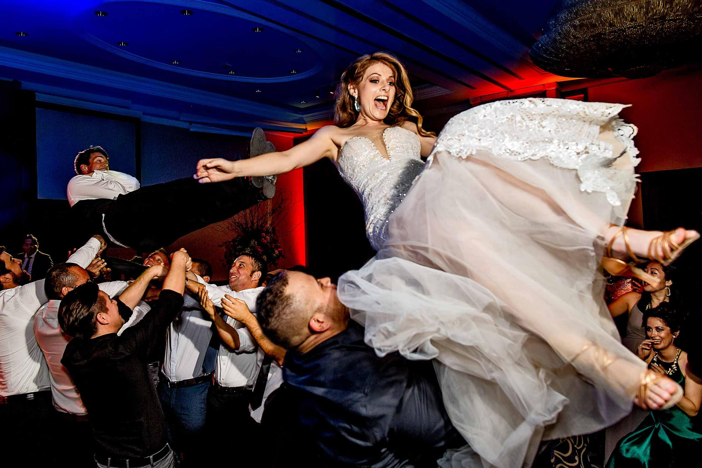 Bride and groom being thrown above friends on the dance floor during their Lima Peru wedding