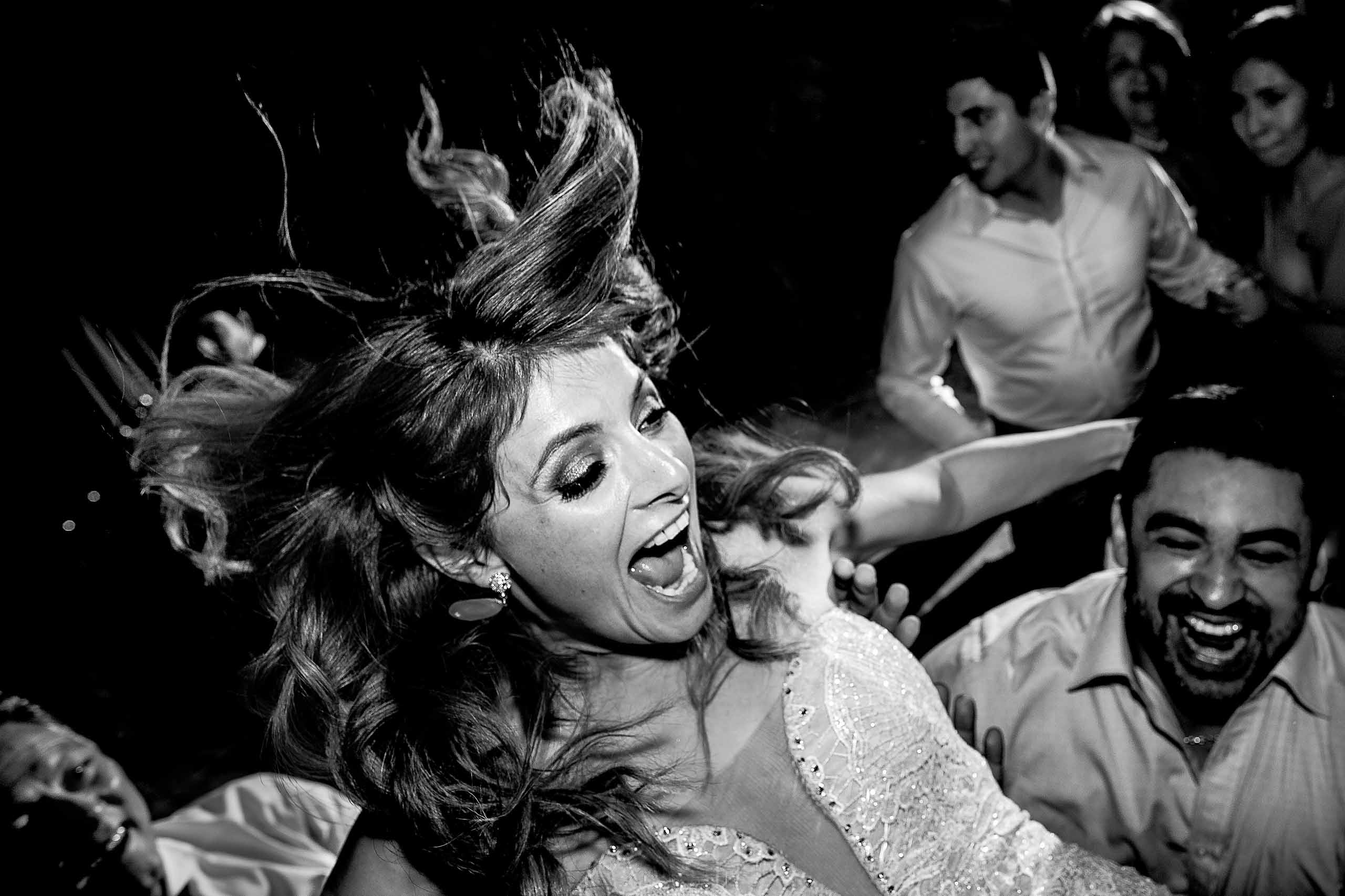 Bride flying high over the guests on the dance floor during her Lima Peru wedding.