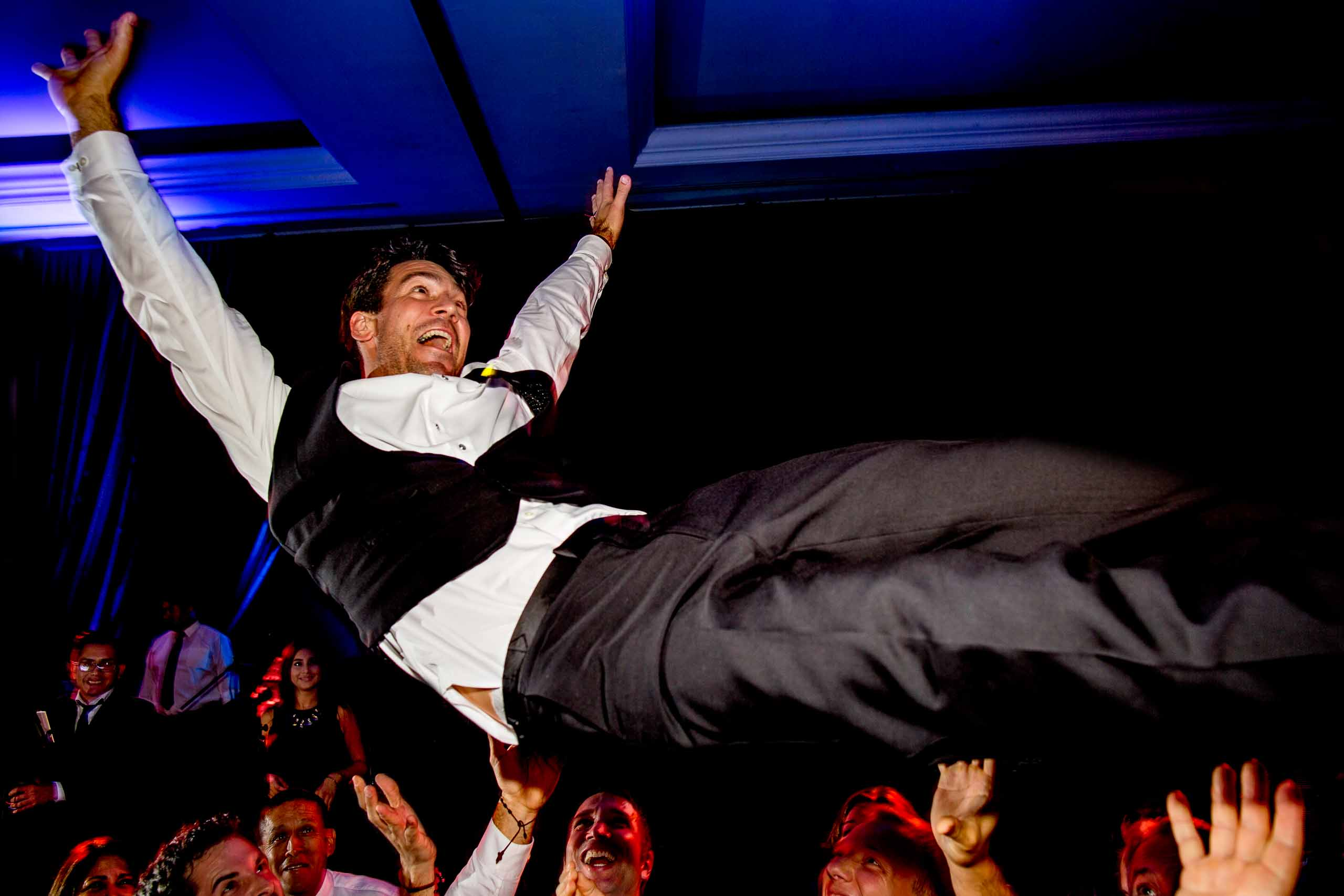 Groom flying high over the guests on the dance floor during their Lima Peru wedding.