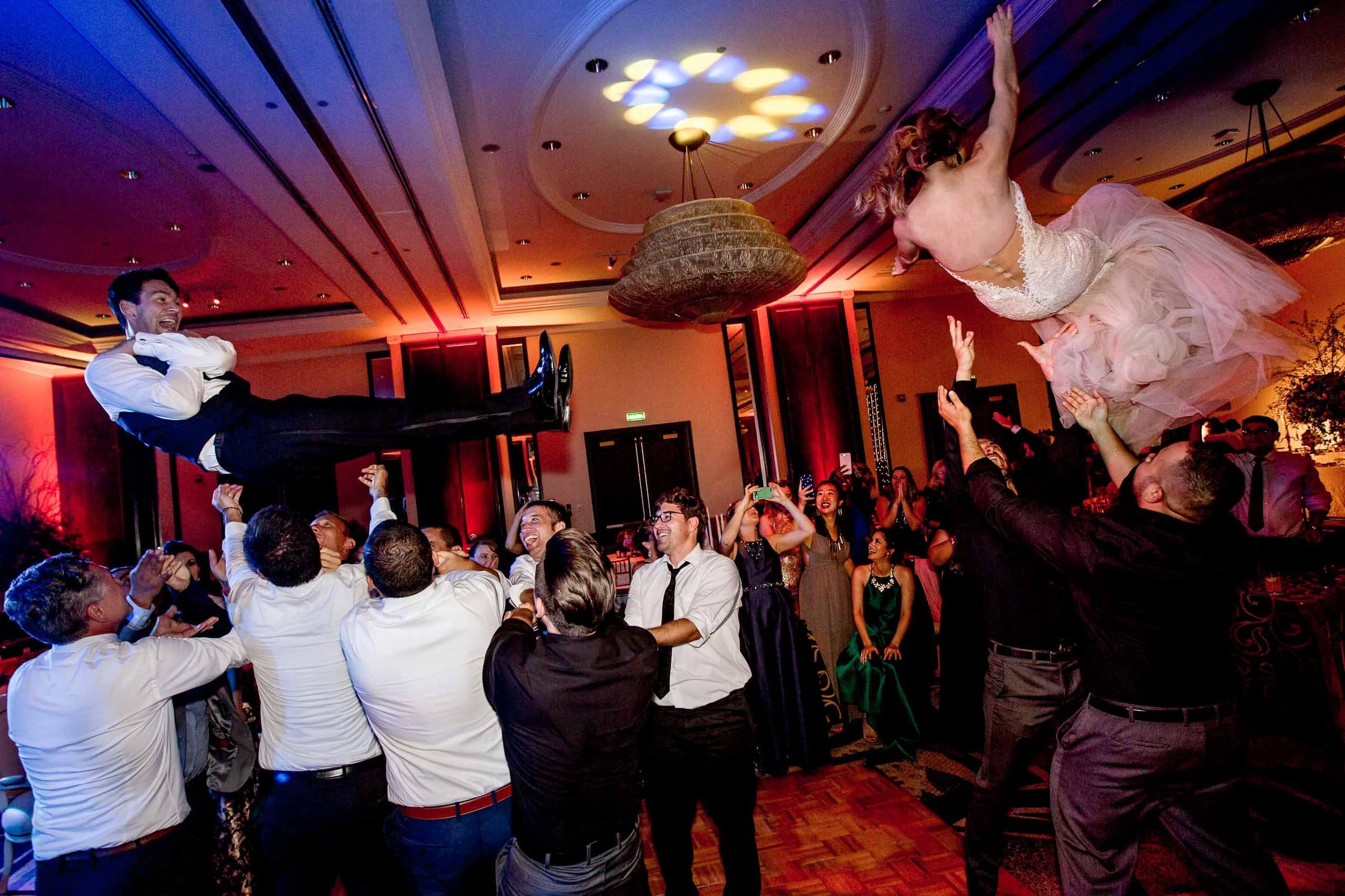 Bride and Groom flying high over their guests on the dance floor during their Lima Peru wedding.