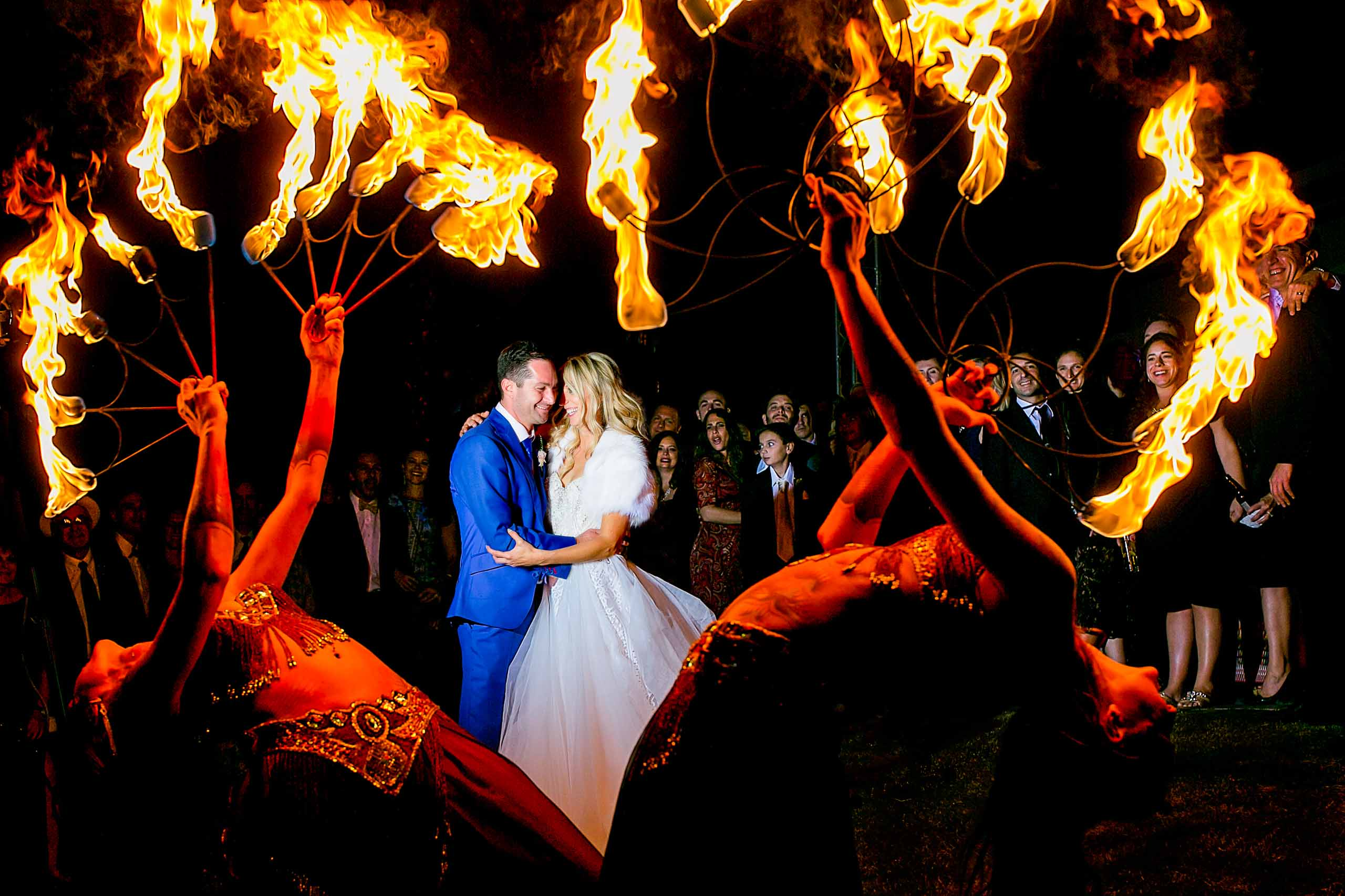 bride and groom surrounded by circus flames lit up perfectly by award winning wedding photographers Jos and Tree