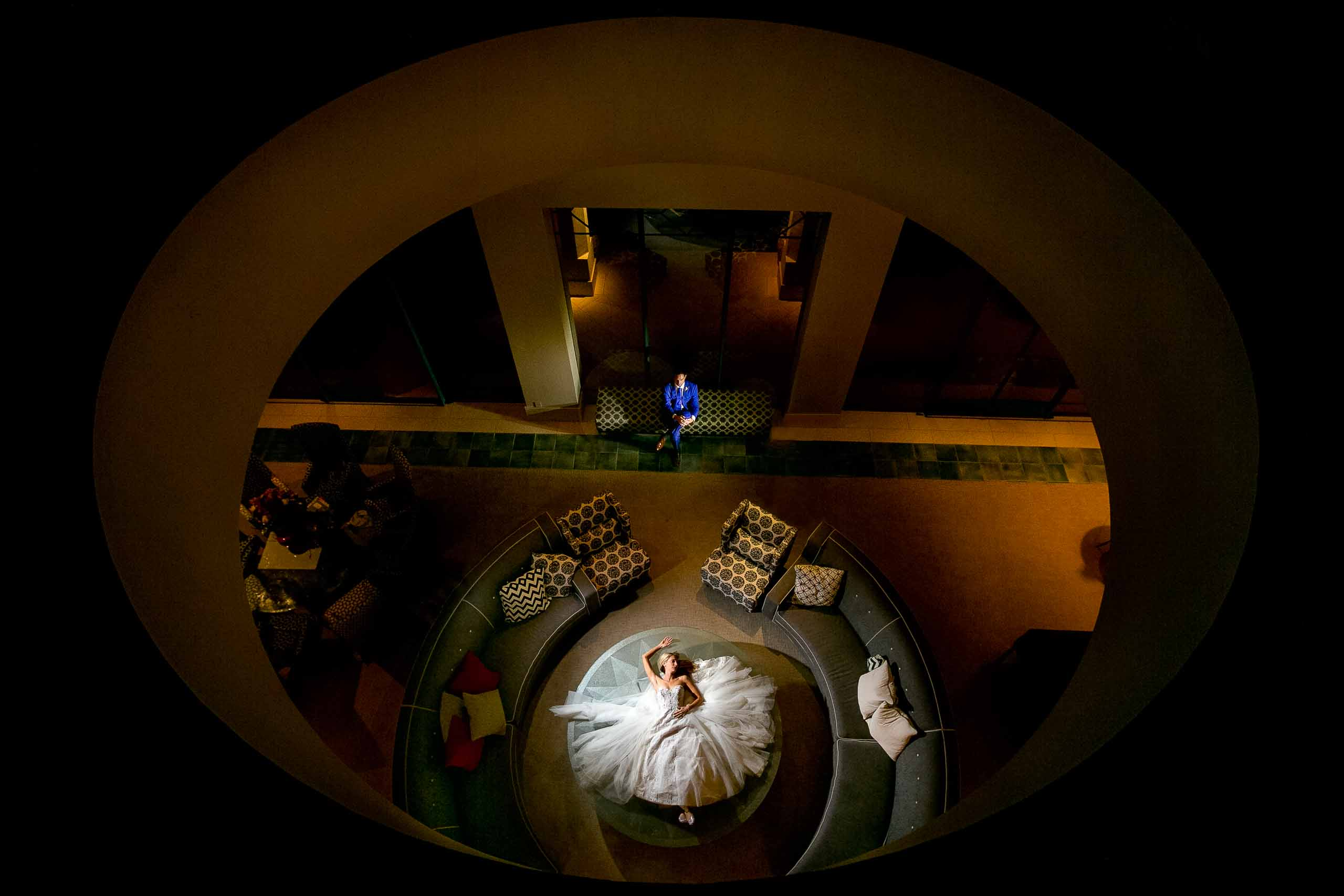 Creative portrait of a bride and groom photographed through a giant skylight window at a Merv Griffin Estate wedding in Palm Springs