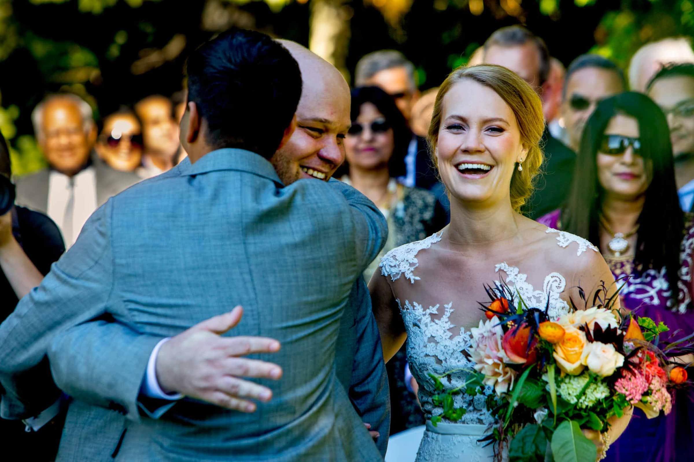 Fun photo of a bride and groom entering a Mt Hood Organic Farms wedding ceremony near Hood River Oregon