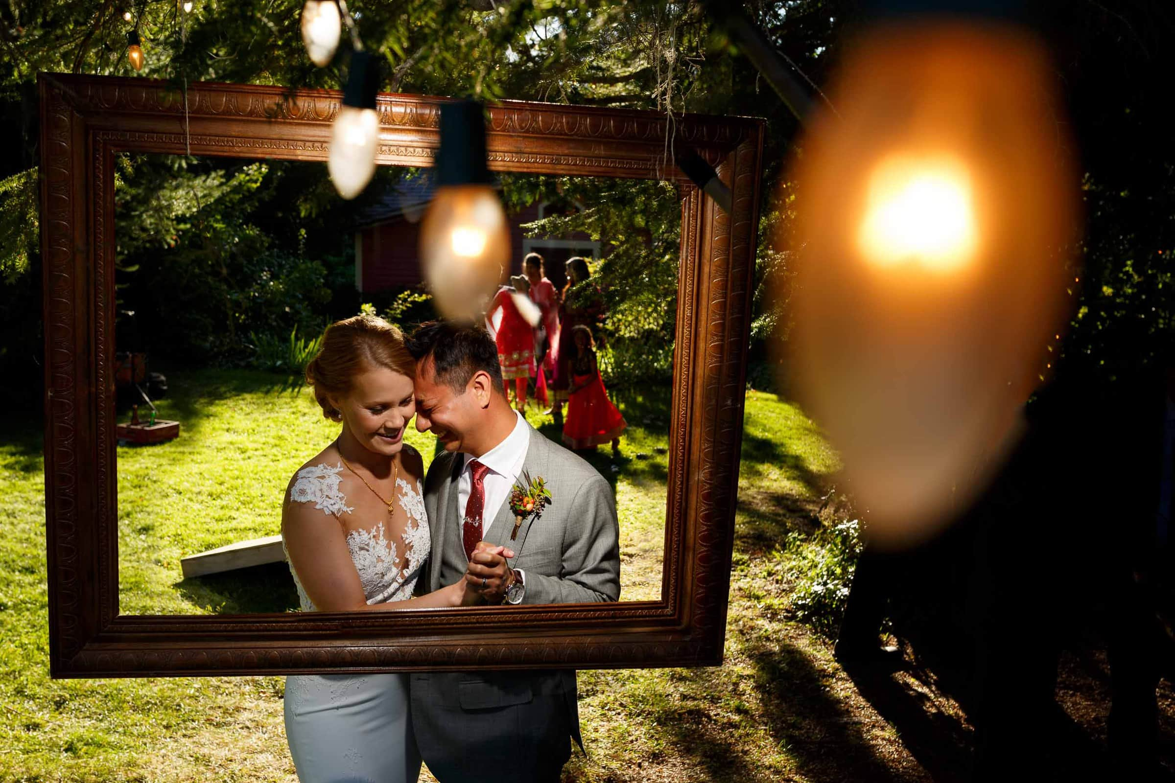 Bride and groom portrait through a picture frame during a Mt Hood Organic Farms wedding reception near Hood River Oregon