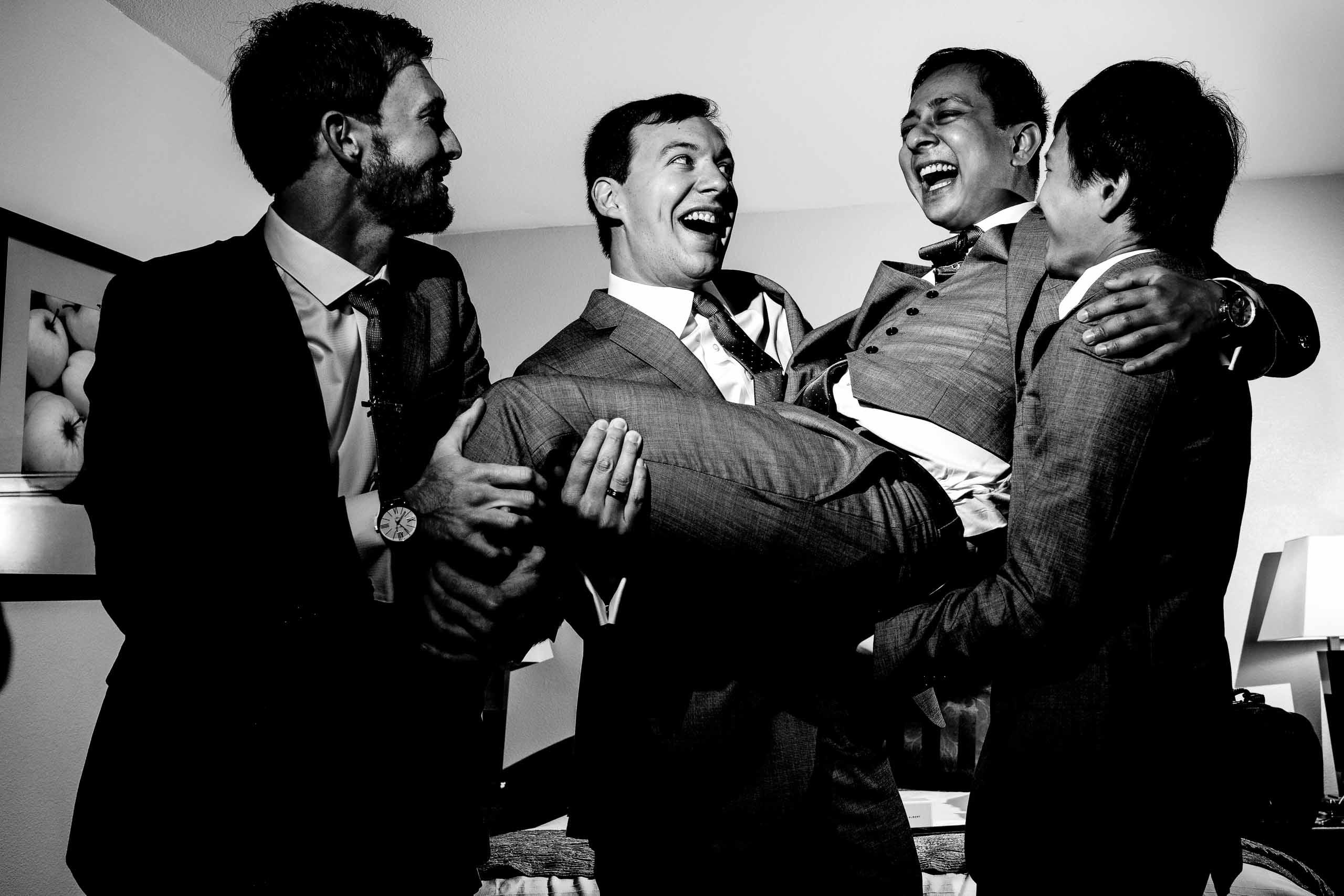 Dramatic off camera flash on groomsmen having fun while getting ready for a Mt Hood Organic Farms wedding in Hood River Oregon