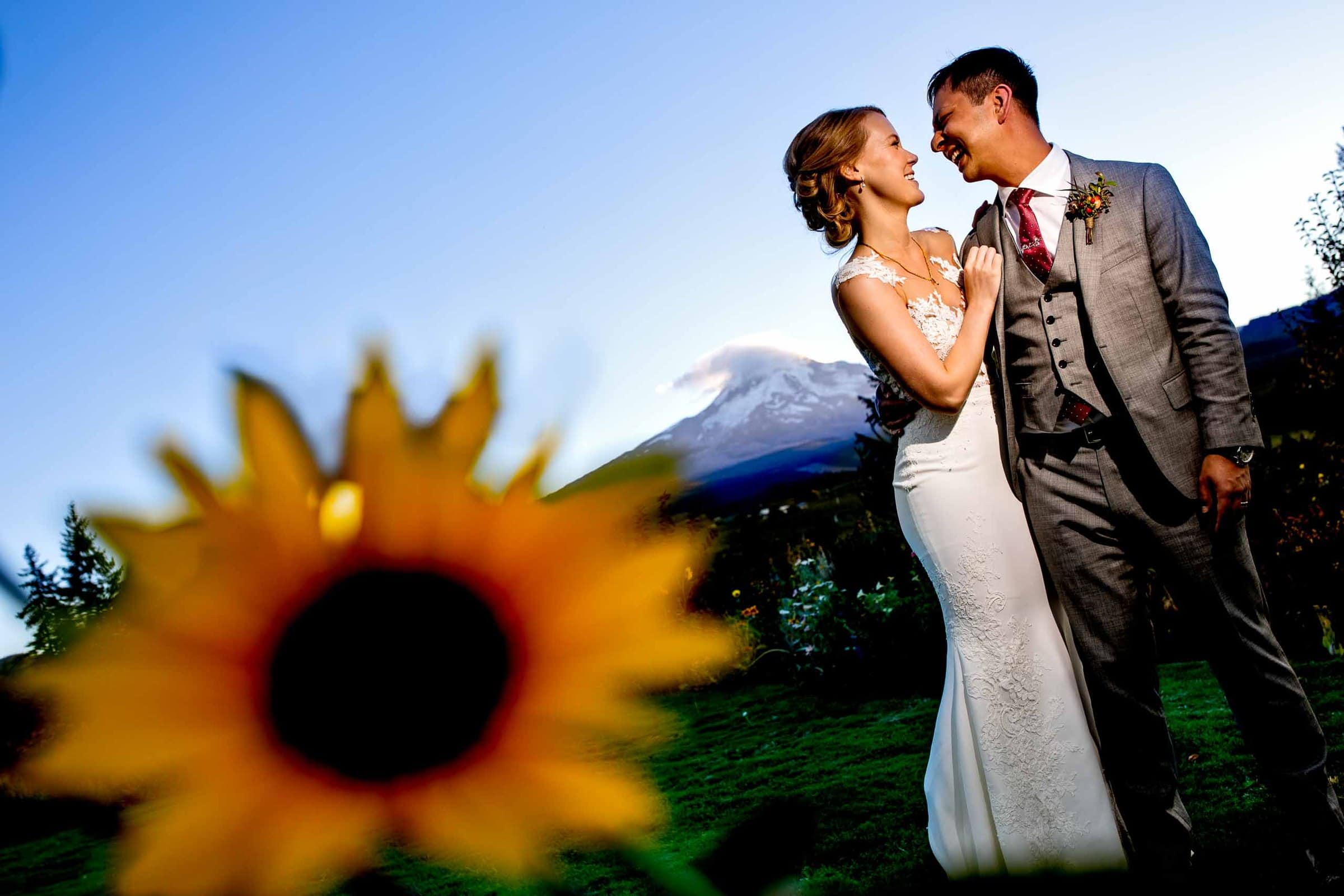 Bride and groom portrait through sun flowers during a Mt Hood Organic Farms wedding reception near Hood River Oregon