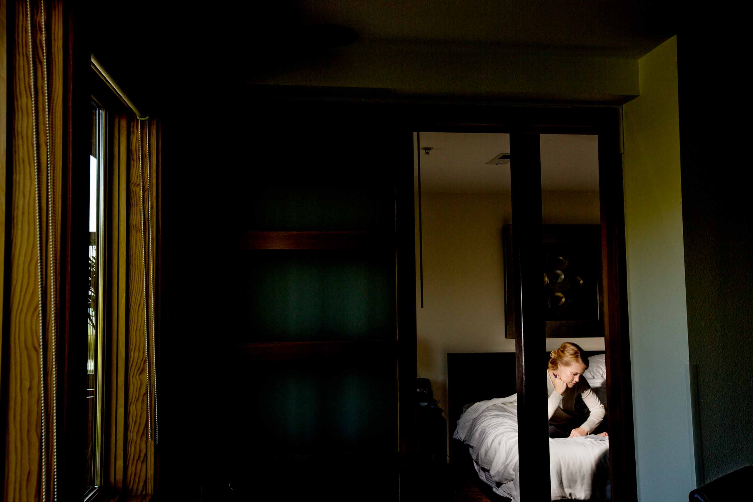 Dramatic off camera flash on a bride studying her vows while getting ready for a Mt Hood Organic Farms wedding in Hood River Oregon