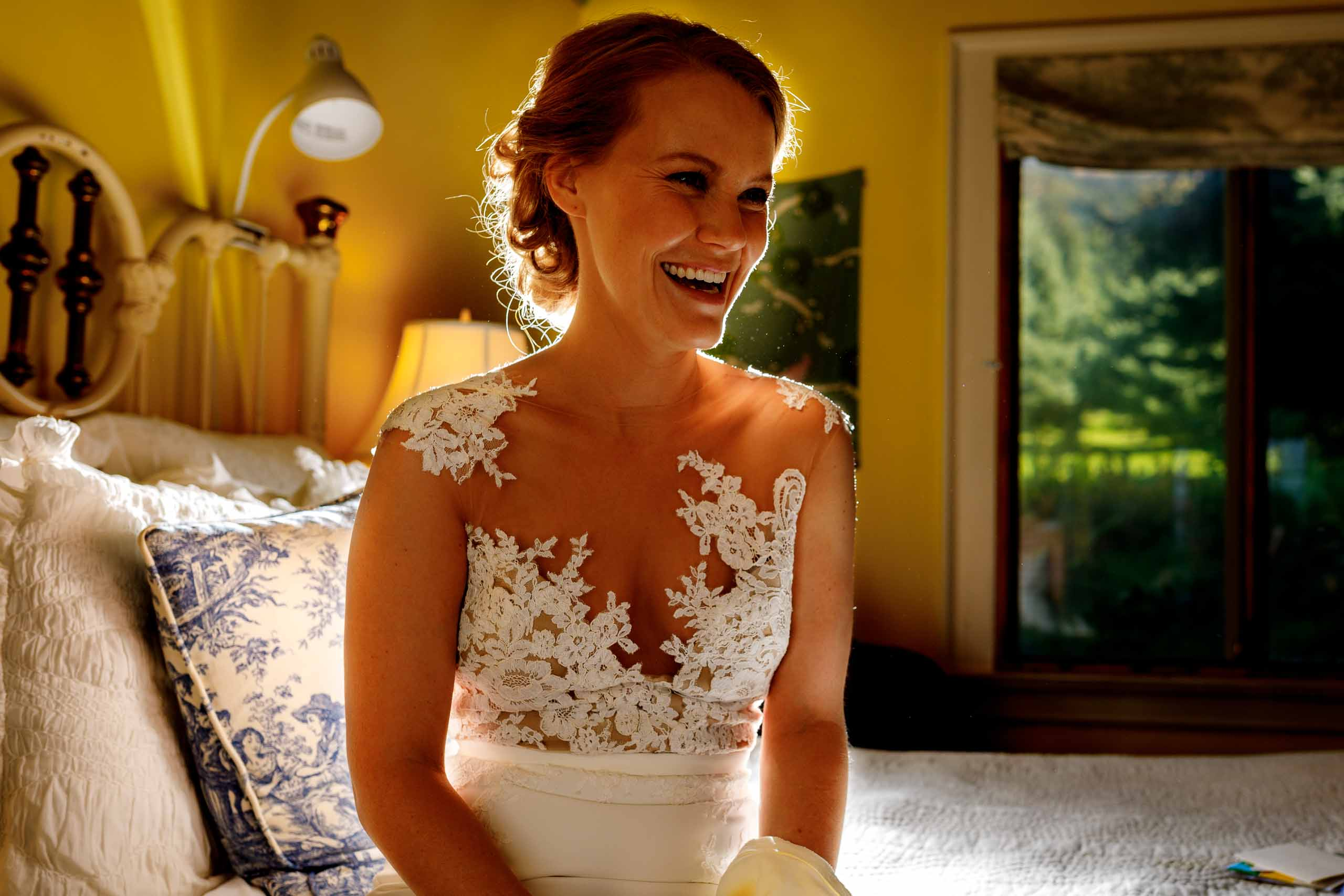 Dramatic off camera flash on a bride laughing while getting ready for a Mt Hood Organic Farms wedding in Hood River Oregon