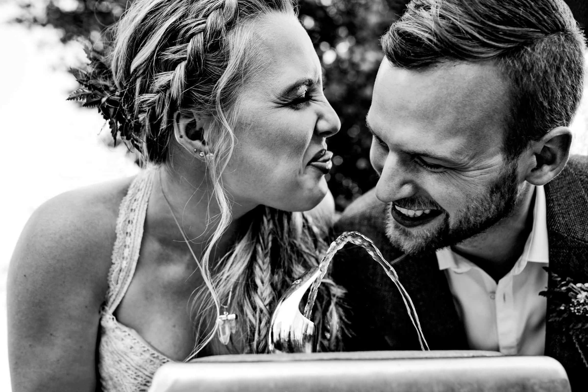 Comical photo of a bride and groom drinking from a fountain in Portland following their Mt Hood Meadows wedding at Umbrella Falls