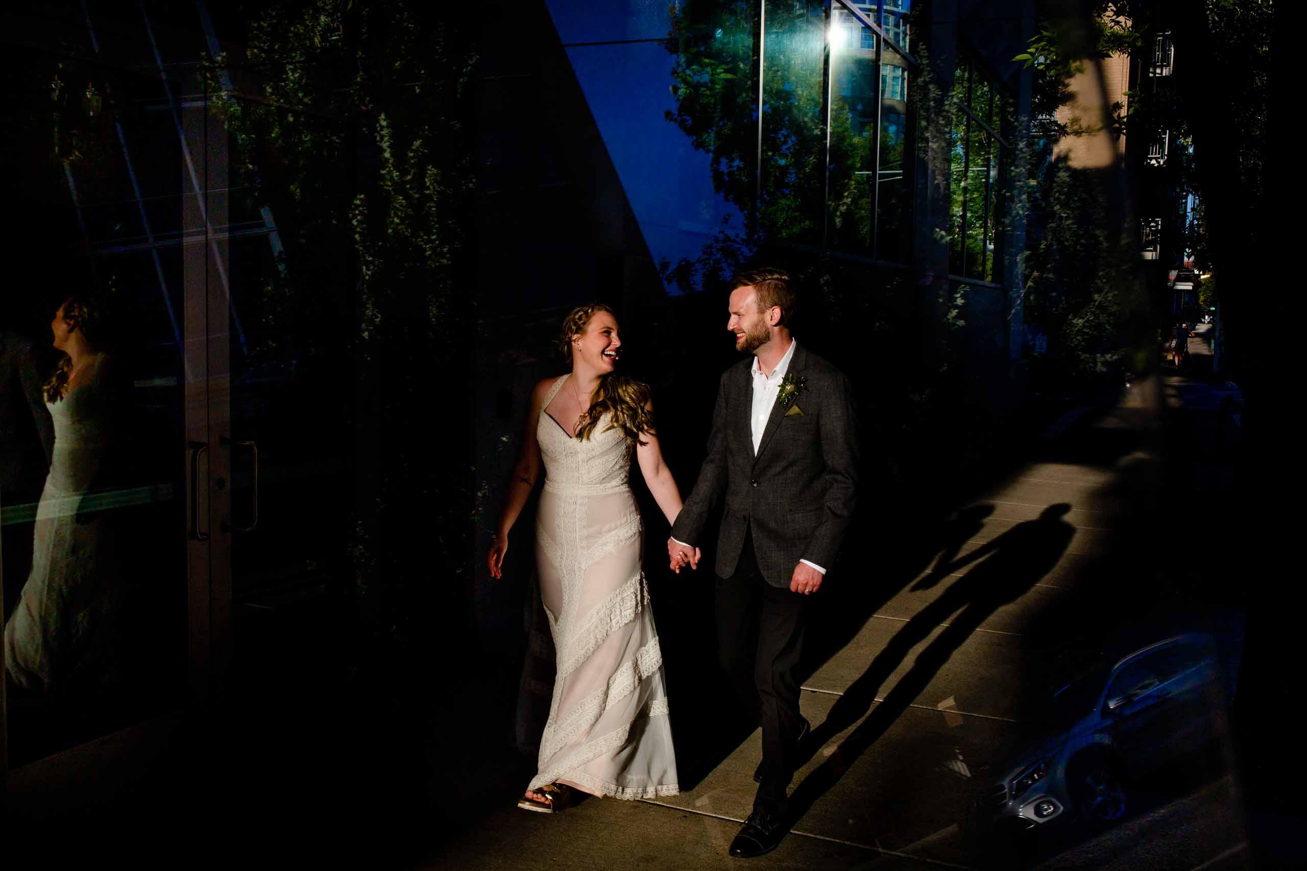Fun photo of bride and groom walking through Portland streets following their Mt Hood Meadows wedding at Umbrella Falls