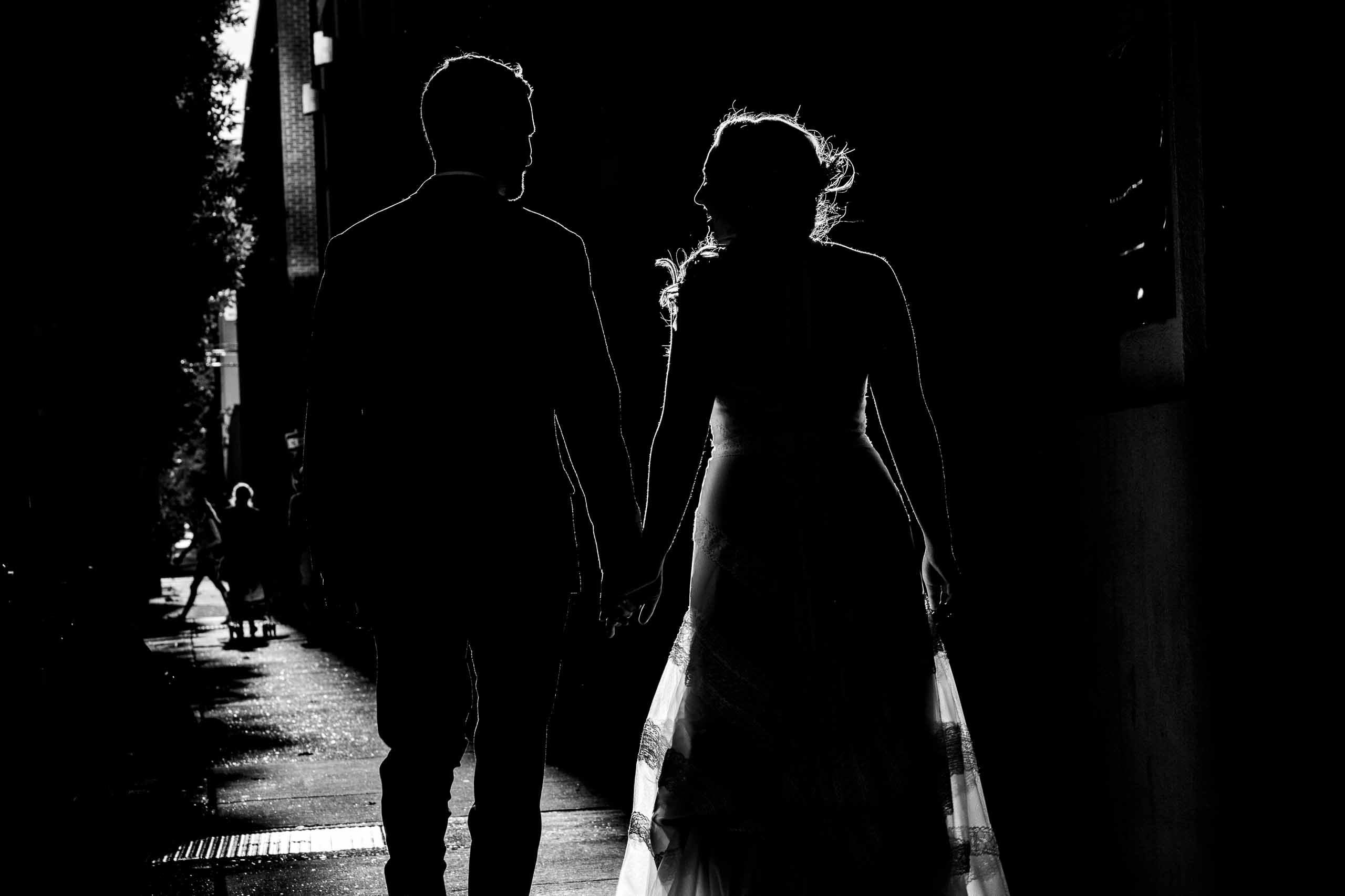 Captivating silhouette photo of bride and groom walking through Portland streets following their Mt Hood Meadows wedding at Umbrella Falls