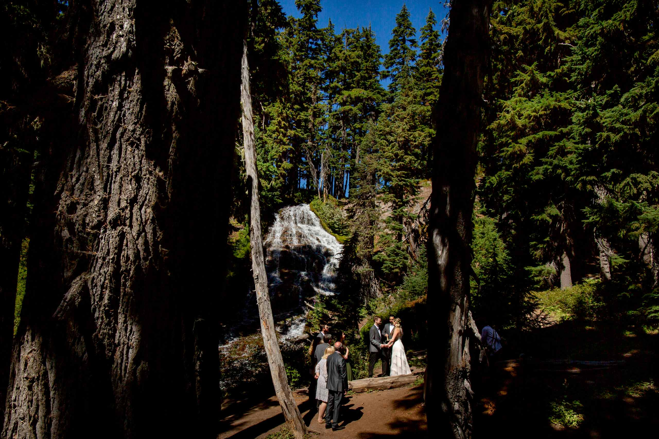 Bride and groom exchanging vows during their Mt Hood Meadows wedding at Umbrella Falls
