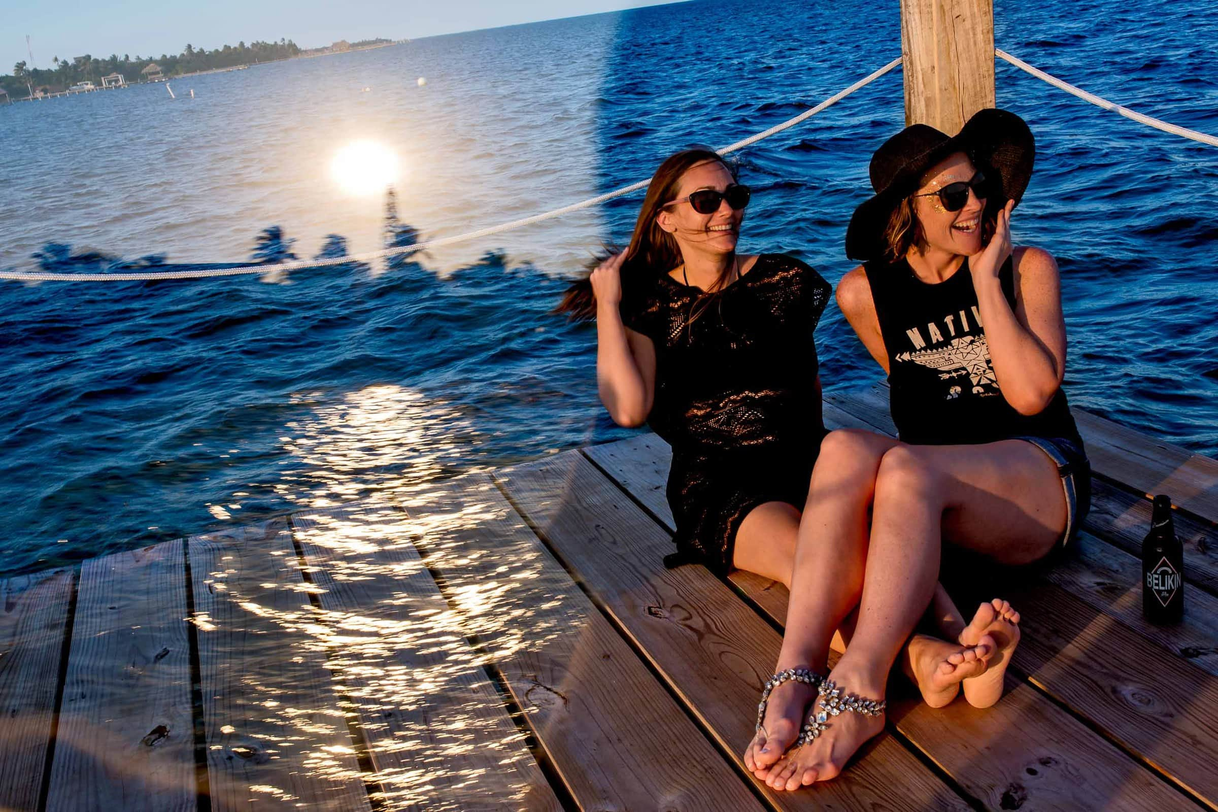 Bride and sister enjoying sunset on a dock the day before Nikki and Paul's Portofino Beach Resort wedding in Belize